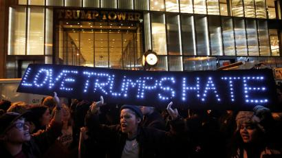 Protestor holds a Love Trumps Hate sign outside of Trump Tower in New York