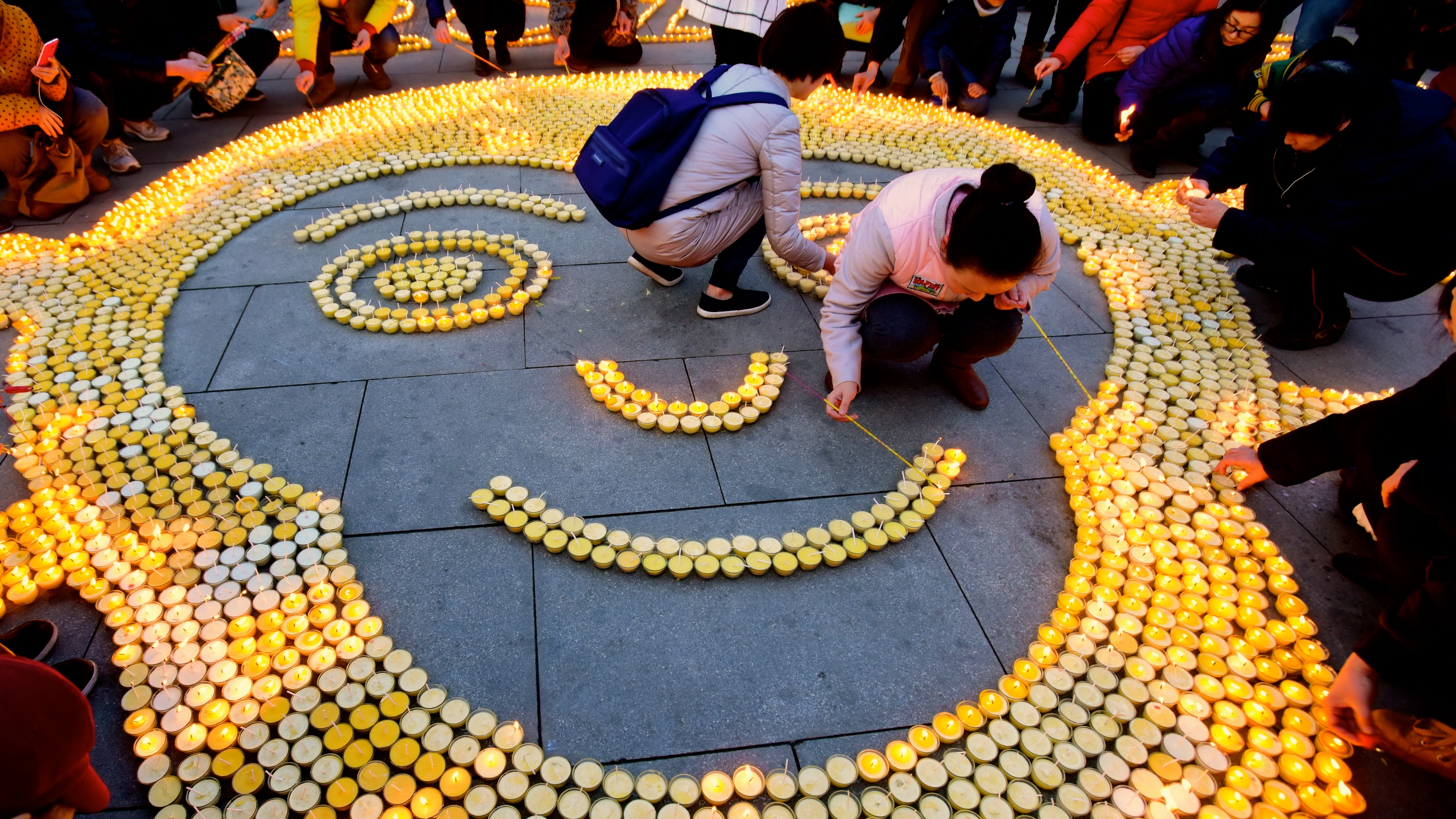People place candles in the shape of a monkey face to pray for good luck at Guangren Temple in China.