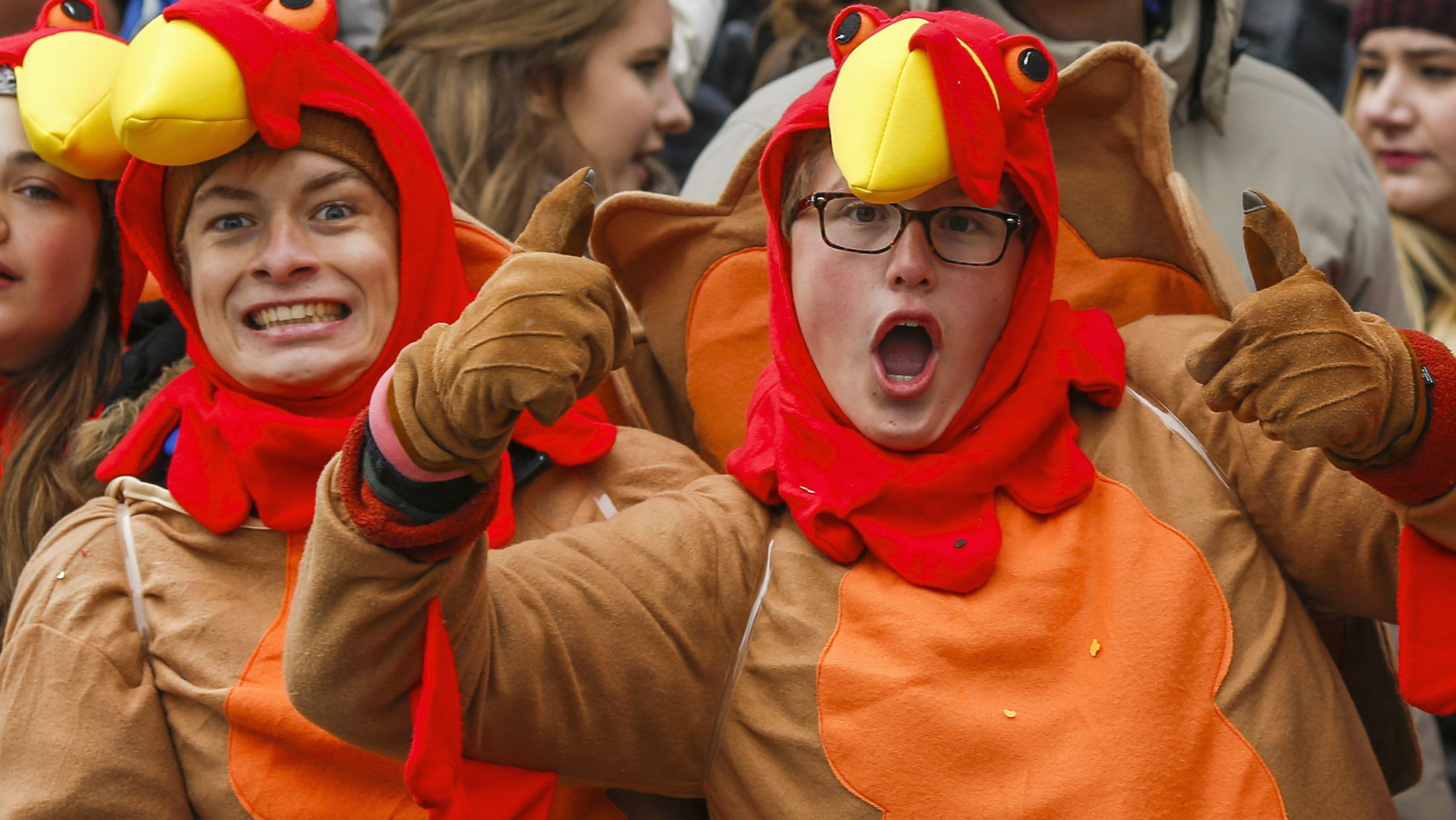 People react as they watch the 88th Macy's Thanksgiving Day Parade in New York November 27, 2014.