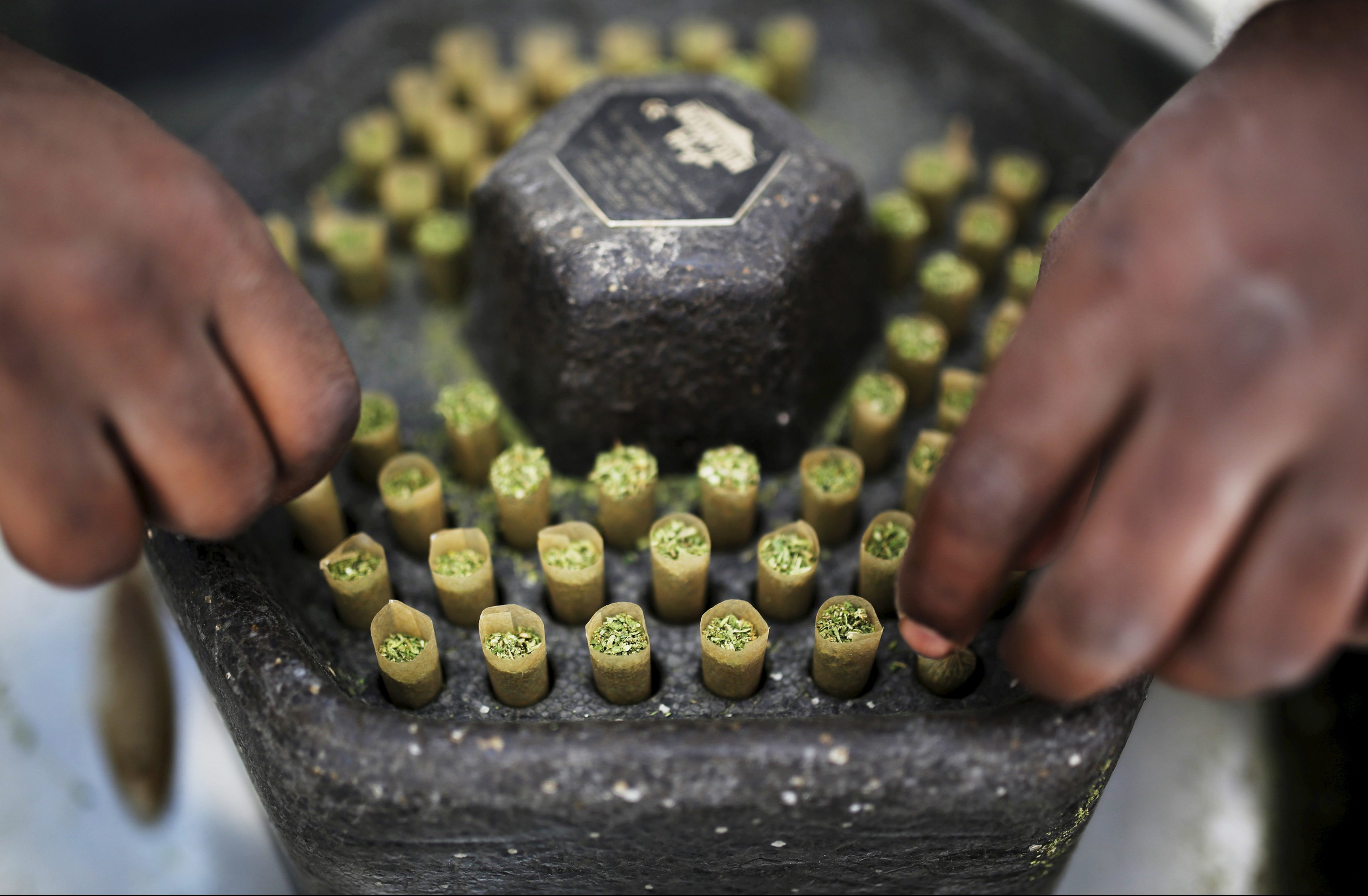 A worker places newly prepared cigarettes filled with medical marijuana at a plantation near the northern Israeli town of Nazareth, in this May 28, 2013 file picture. REUTERS/Amir Cohen/Files - RTSCMIK
