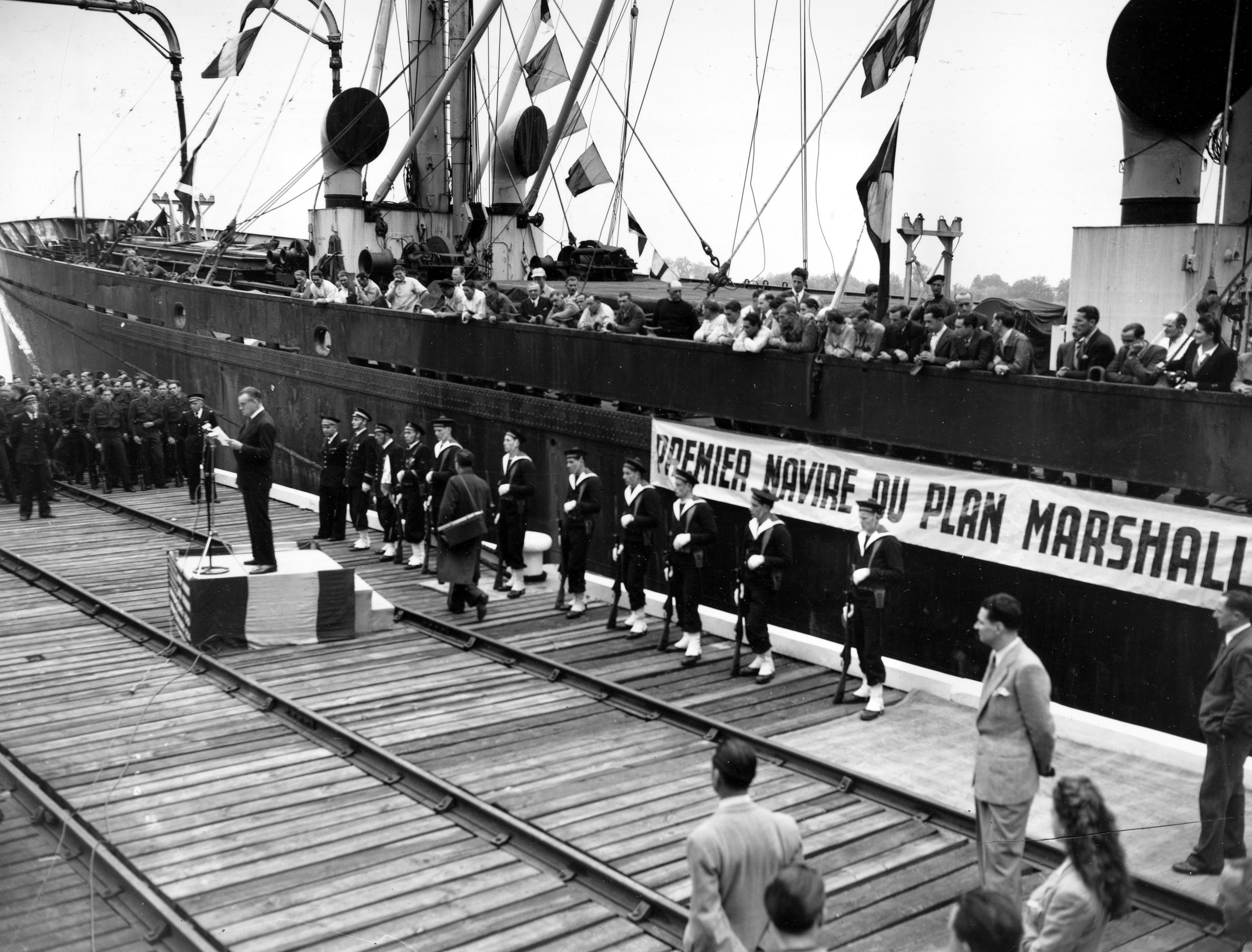 """American ambassador to France, Jefferson Caffery, speaks during a ceremony at the harbor of Bordeaux, France, on May 10, 1948. The celebration is marking the arrival of the """"John H. Quick,"""" carrying 8,800 tons of wheat as the first ship bringing aid to France under the Marshall Plan."""