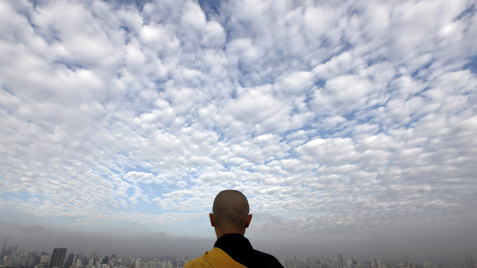 Buddhist monk Jisho Handa from the Busshinji temple, meditates on the helipad of Copan building in downtown Sao Paulo February 18, 2011. Buddhist monks from the Busshinji temple in Sao Paulo meditate once a month on top of the 37-story high Copan building, one of the tallest in Sao Paulo. Monks want to take meditation from the temple to the streets and they consider Copan building, created by renowned Brazilian architect Oscar Niemeyer, a zen Buddhist mountain in the middle of the city. REUTERS/Nacho Doce (BRAZIL - Tags: RELIGION CITYSCAPE SOCIETY) - RTR2ISPY