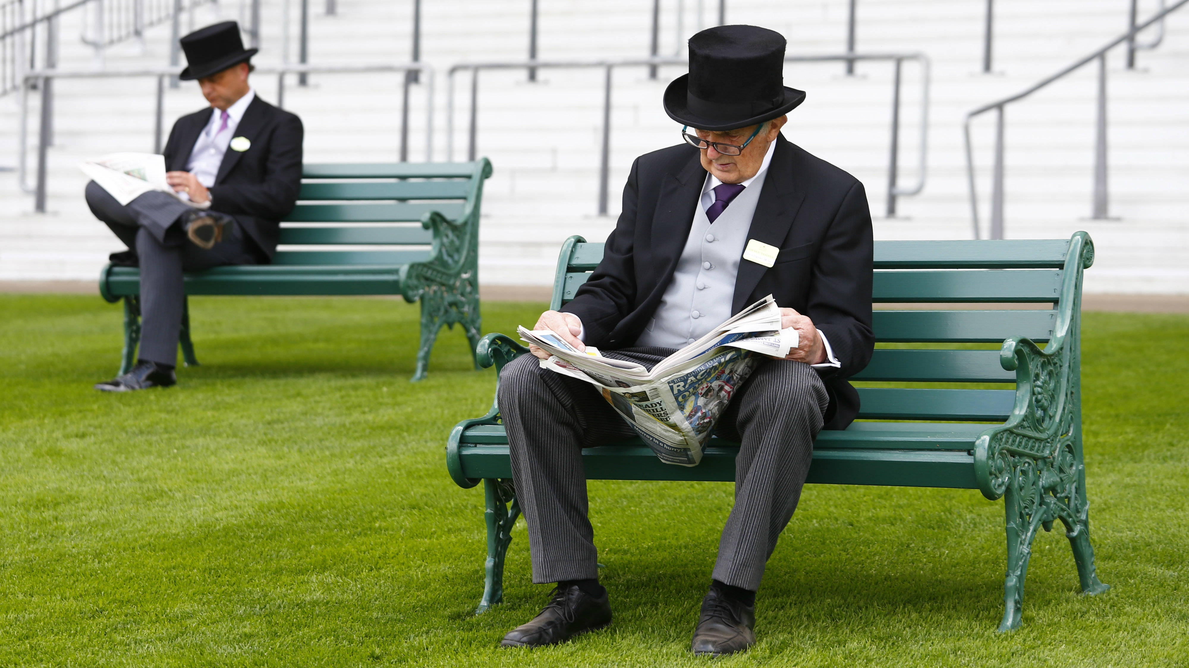 Men in traditional suits reading newspapers