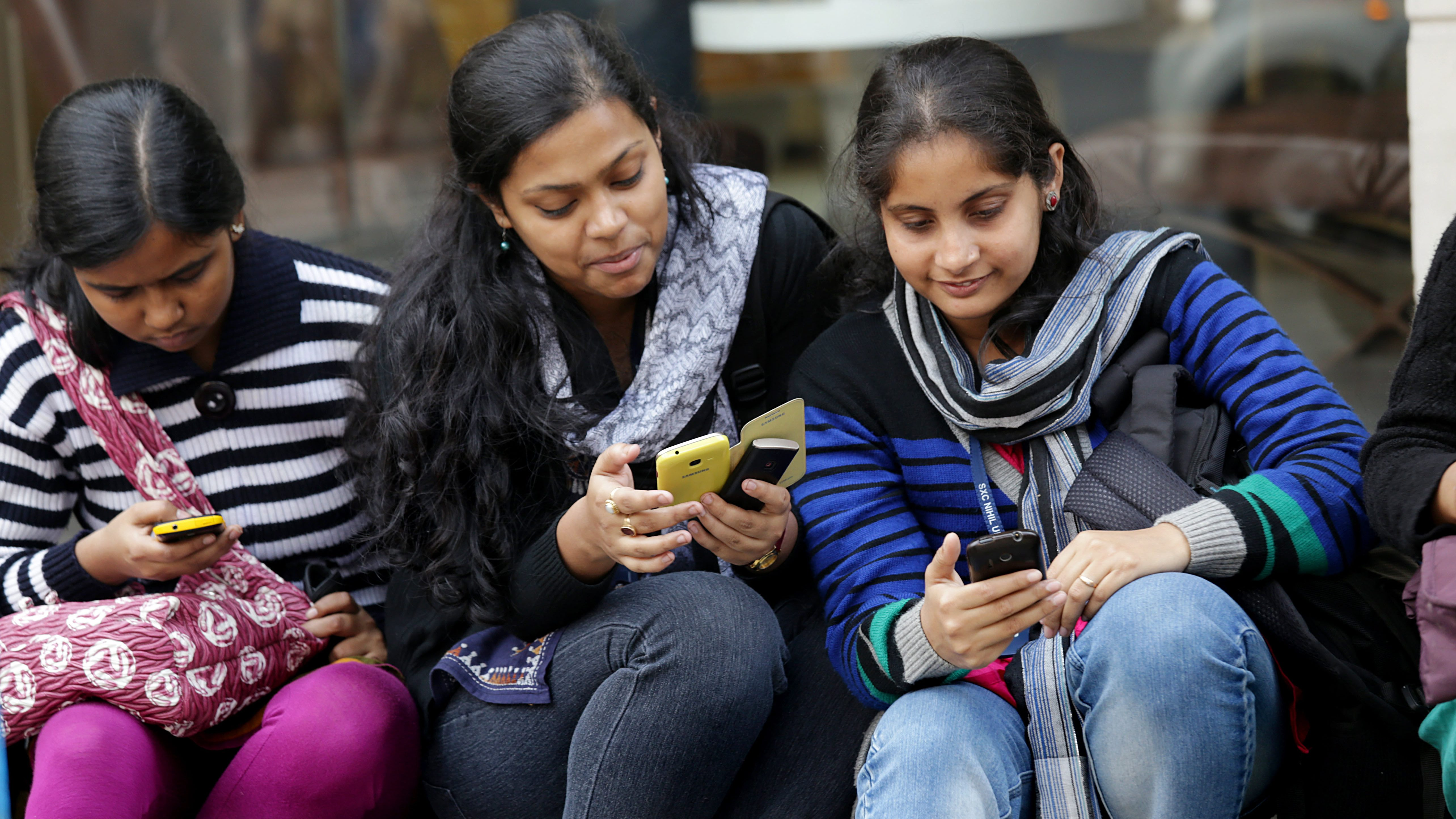 Indian students browse the internet with their smartphone.