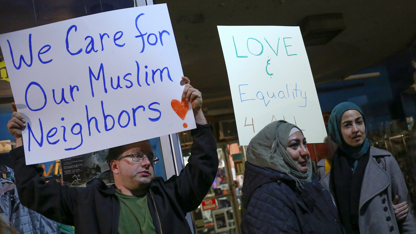 Demonstrators hold signs during a protest against President-elect Donald Trump and in support of Muslims residents in downtown Hamtramck, Michigan, U.S. on November 14, 2016.    REUTERS/Brittany Greeson - RTX2TOIU