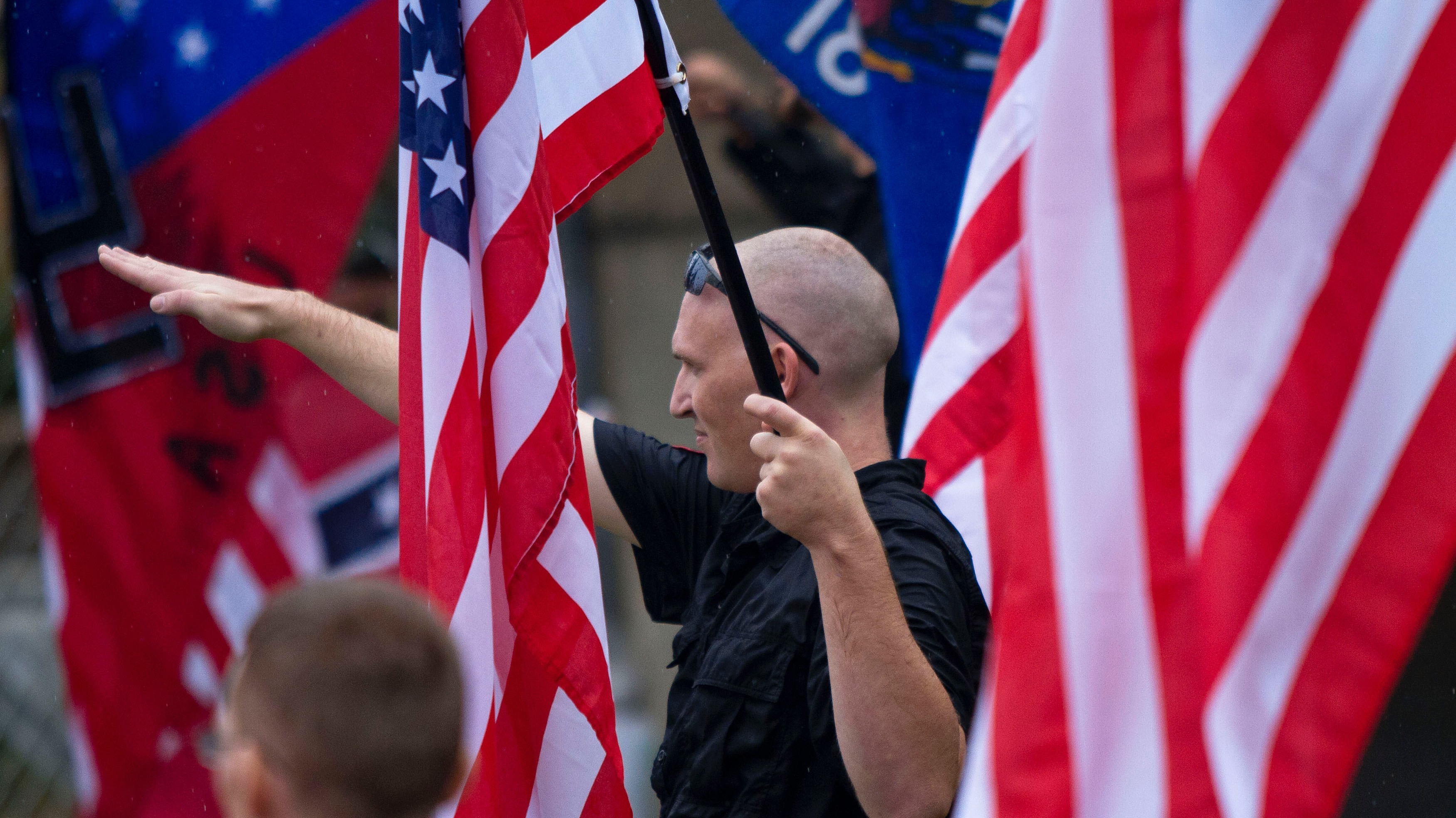 """A member of a white supremacy group gives the fascist salute during a gathering in West Allis, Wisconsin, September 3, 2011. Neo-Nazi demonstrators gathered for a """"rally in defense of white America"""" in response to an incident that Milwaukee Police Chief described as racially charged violence outside the Wisconsin state fair on August 4, 2011. REUTERS/Darren Hauck (UNITED STATES) REUTERS/Darren Hauck (UNITED STATES - Tags: POLITICS CIVIL UNREST SOCIETY) - RTR2QRBL"""