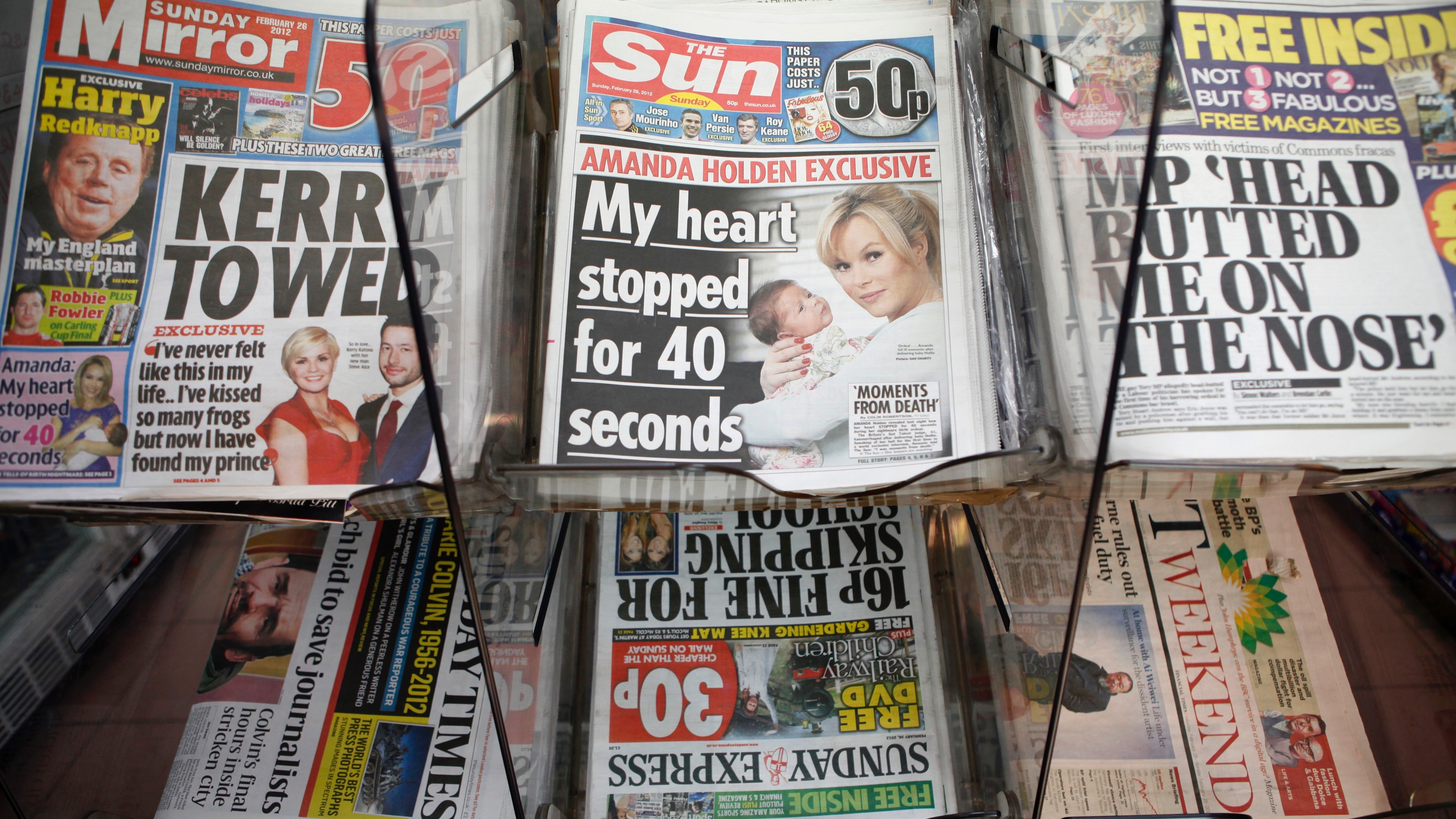 Copies of the Sun on Sunday are displayed for sale, on the first day of publication, in a  newsagents in Wembley, north London February 26, 2012. Rupert Murdoch bid to grab back the huge audience his News Corp lost when it closed Britain's best-selling News of the World over a phone-hacking scandal with a new Sunday edition of his Sun tabloid filled with gossip, girls and celebrities.  REUTERS/Andrew Winning    (BRITAIN - Tags: MEDIA BUSINESS SOCIETY) - RTR2YGUI
