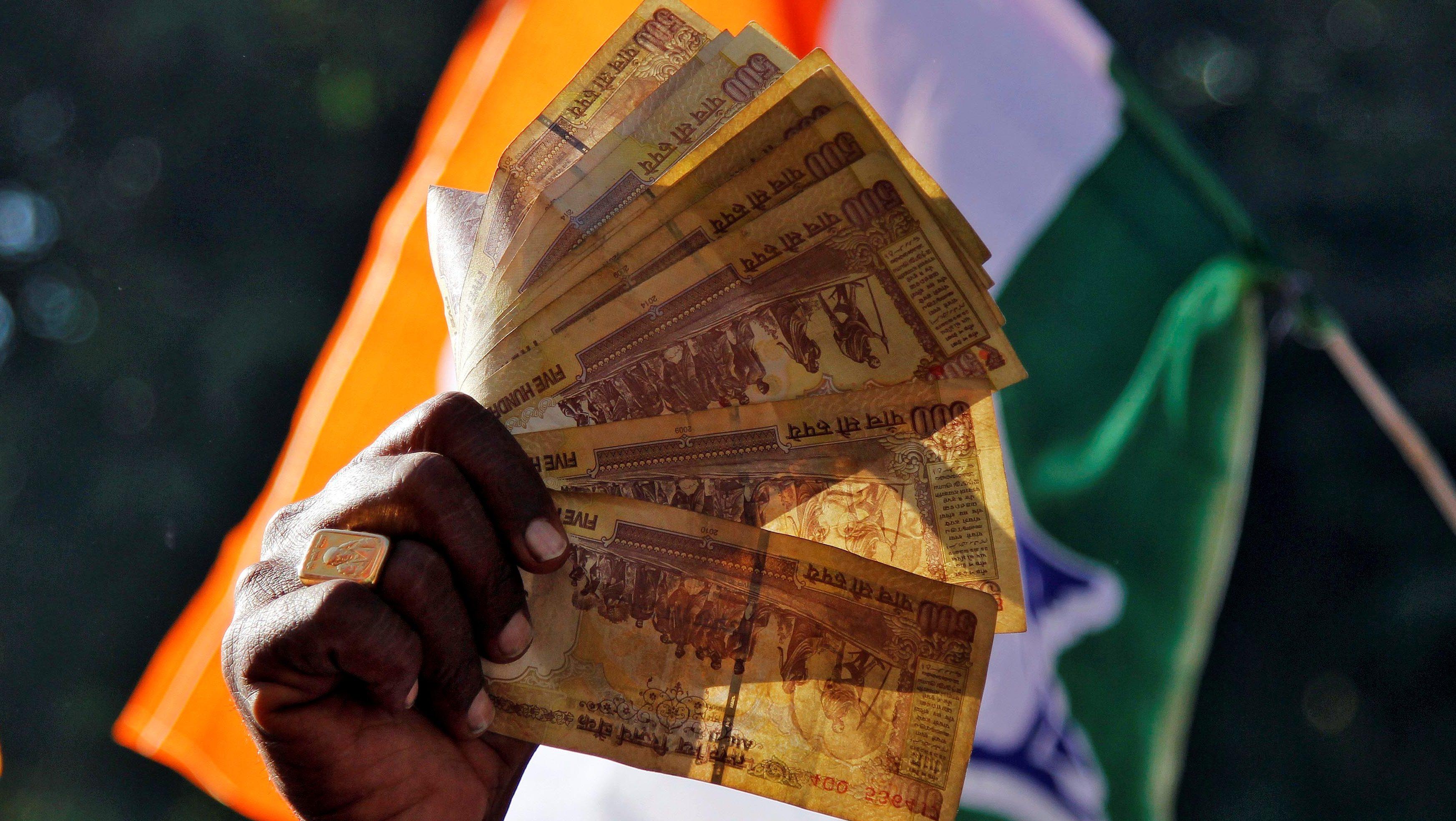 A man displays 500 Indian rupee notes