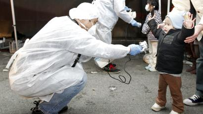 A Japanese official checks a child for radiation exposure.
