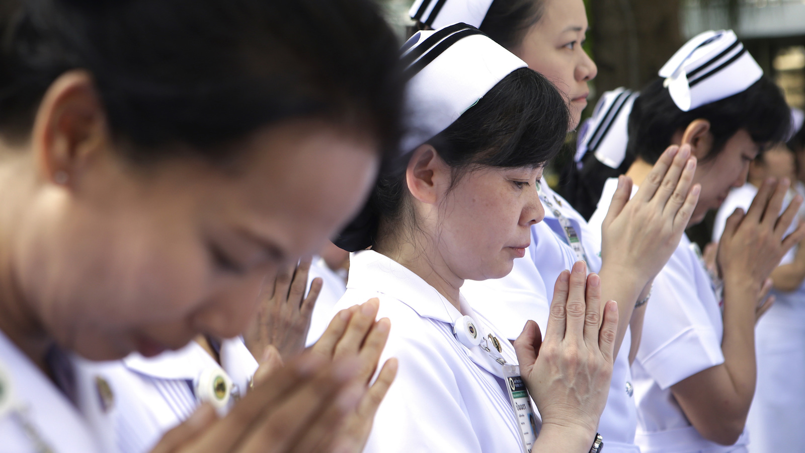Mourners nurses pray before stand silent memorial service at Siriraj Hospital for one week anniversary the late Thai King Bhumibol Adulyadej in Bangkok, Thailand, Thursday, Oct. 20, 2016. King Bhumibol died last Thursday at age 88. (AP Photo/Sakchai Lalit)