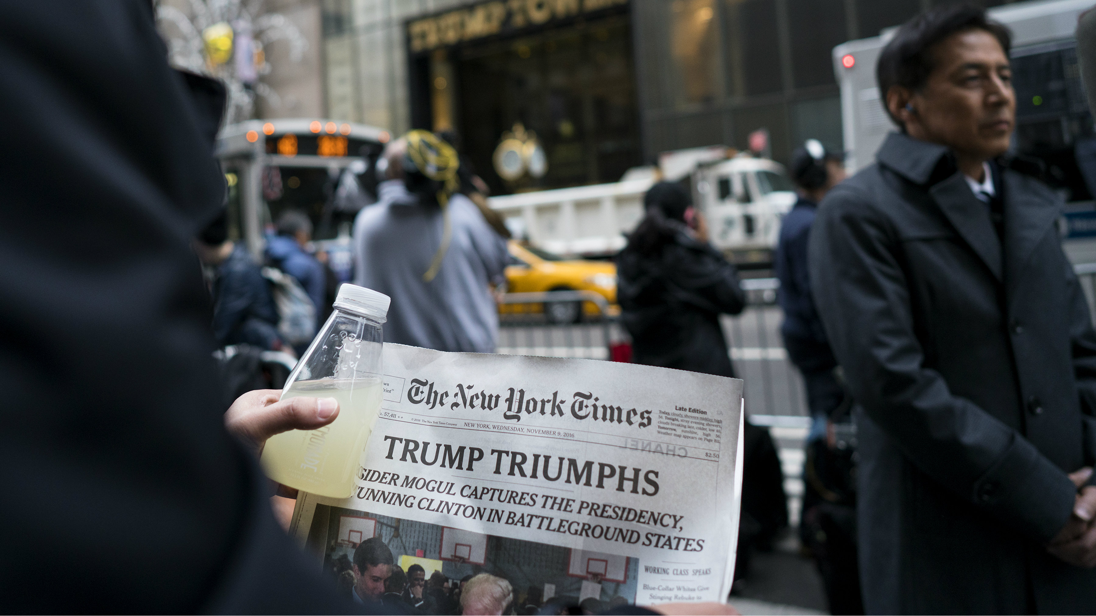 A person holds a newspaper signaling President-elect Donald Trump's victory across 5th Ave. from Trump Tower in New York Wednesday, Nov. 9, 2016.