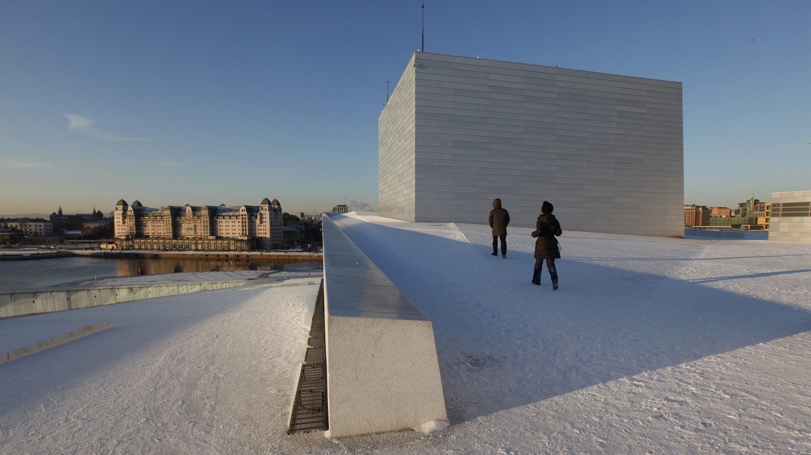Pedestrians walk around the Opera House during winter in Oslo December 11, 2012. REUTERS/Suzanne Plunkett (NORWAY - Tags: ENTERTAINMENT CITYSCAPE ENVIRONMENT) - RTR3BGCL