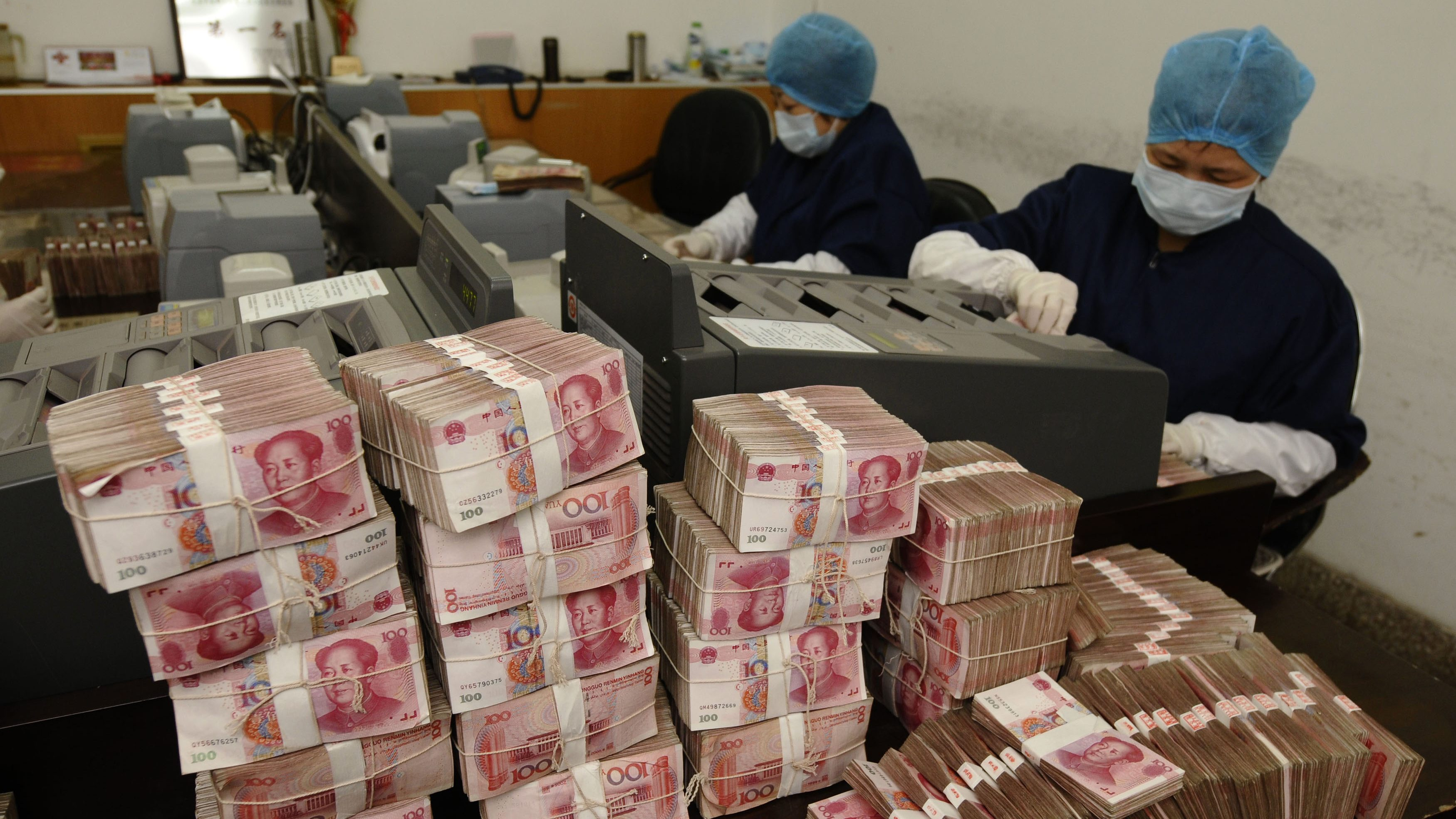 Employees count yuan banknotes at a branch of Bank of China in Changzhi