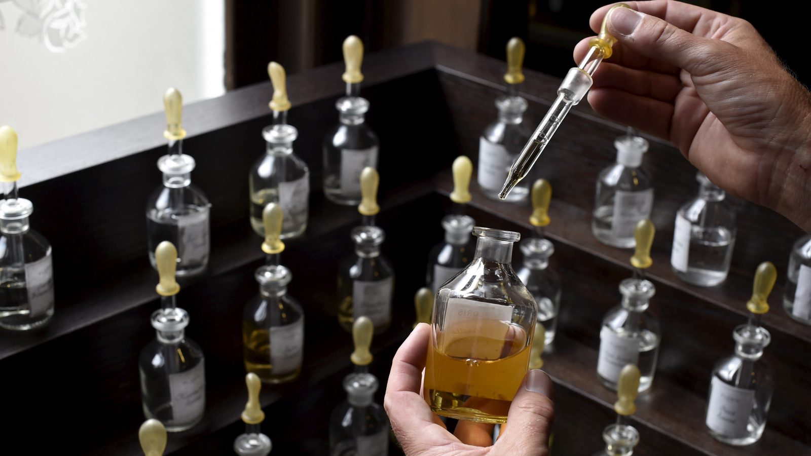 Director of perfumer Floris, Edward Bodenham, holds a pipette of vanilla as he mixes ingredients in his store in central London, Britain, August 19, 2015. Floris, established in 1730, holds a warrant as perfumer to Queen Elizabeth. Every year Queen Elizabeth grants about 20 royal warrants, the gold emblem of the British monarchy, in a practice dating back to medieval times. The warrant holders can display the certificate and use the royal coat of arms in their marketing. The warrants lasting five years can help businesses break into new markets overseas, using their role as supplier to the royal family as a gauge of quality. On September 9, Queen Elizabeth will overtake Queen Victoria as Britain's longest-serving monarch. Picture taken August 19, 2015. REUTERS/Toby Melville - RTX1QPS6