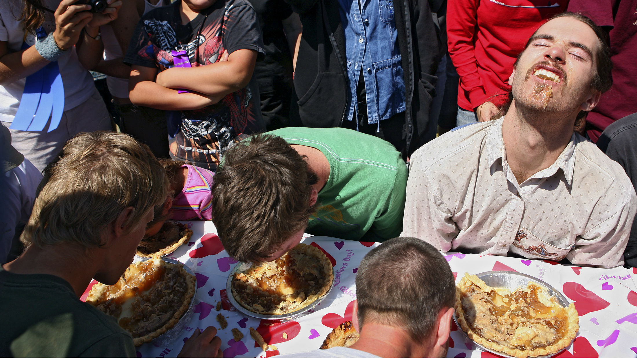 A scene from a pie eating contest in which contestants can only eat with their faces.