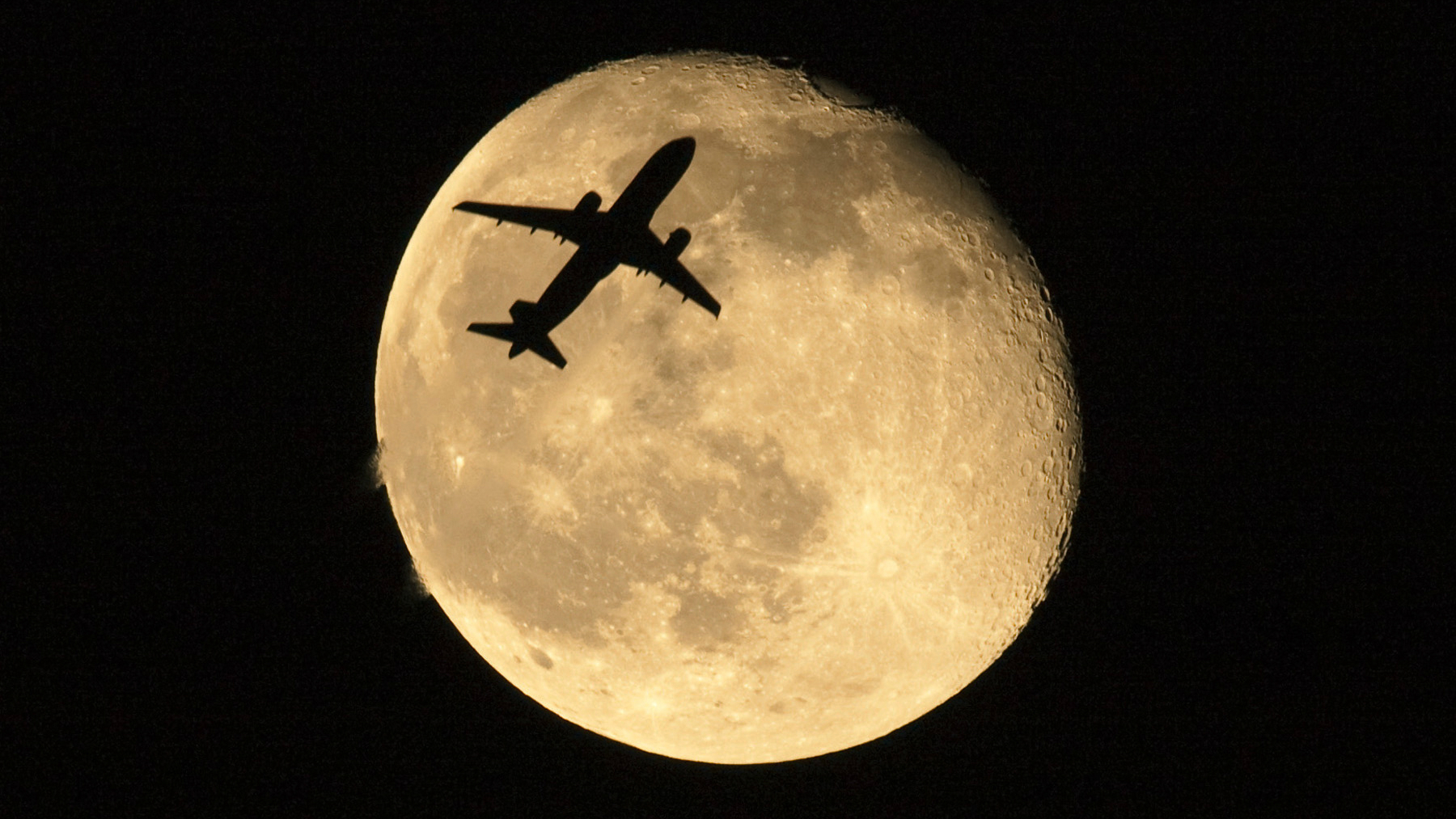 Plane in front of the moon.