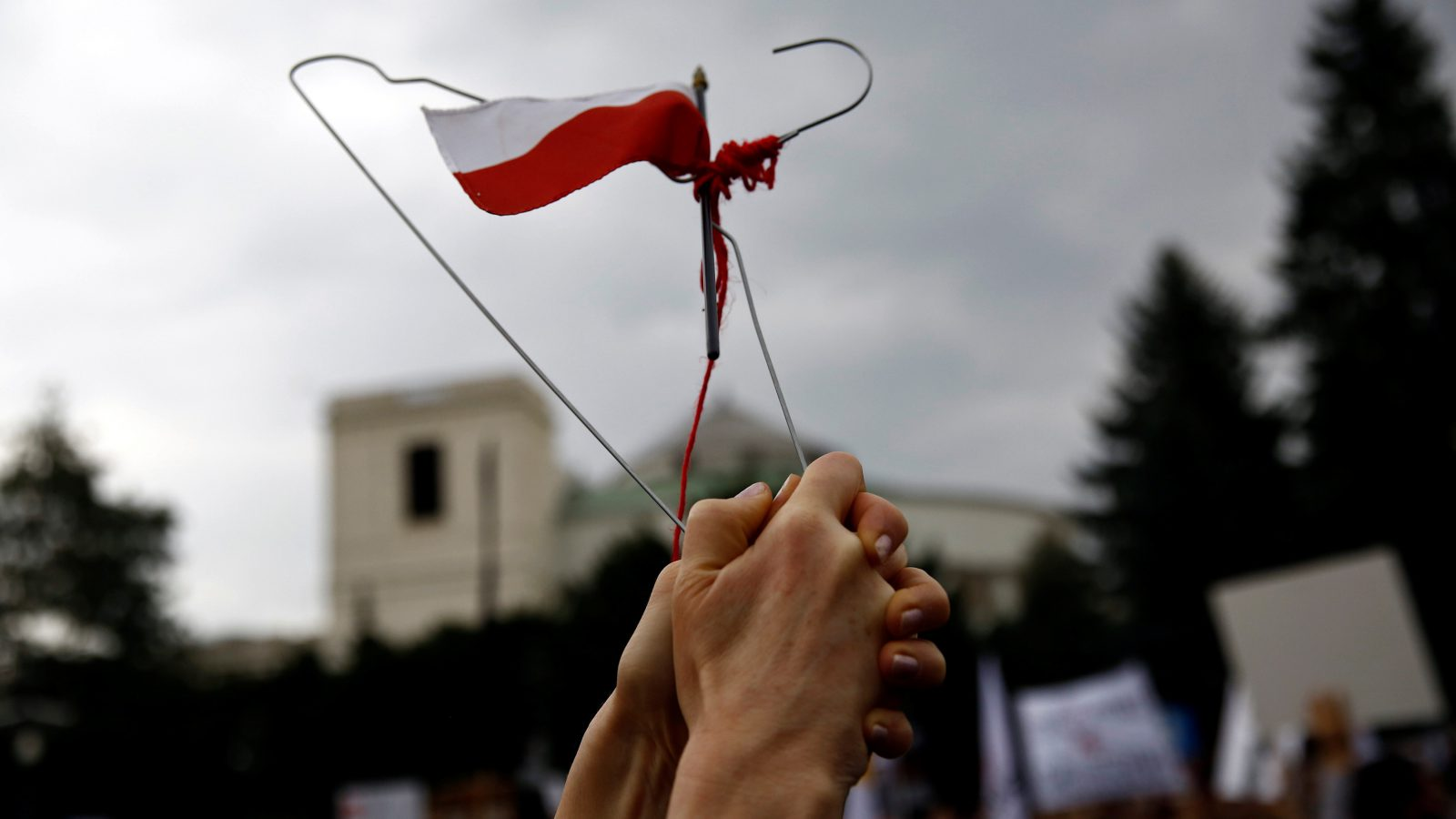 """A woman holds a hanger with the Polish flag attached to it as she takes part in an abortion rights campaigners' demonstration """"Black Protest"""" in front of the Parliament in Warsaw, Poland October 1, 2016. REUTERS/Kacper Pempel - RTSQBYQ"""