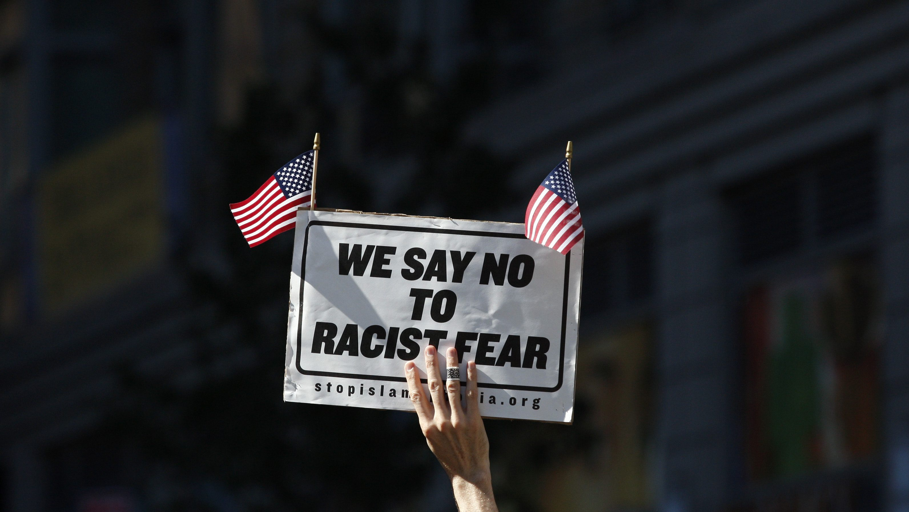 A demonstrator holds a sign above his head during a rally held in support of a proposed Islamic cultural centre and mosque in New York September 11, 2010. REUTERS/Jessica Rinaldi (UNITED STATES - Tags: SOCIETY POLITICS CIVIL UNREST RELIGION IMAGES OF THE DAY) - RTR2I7P8