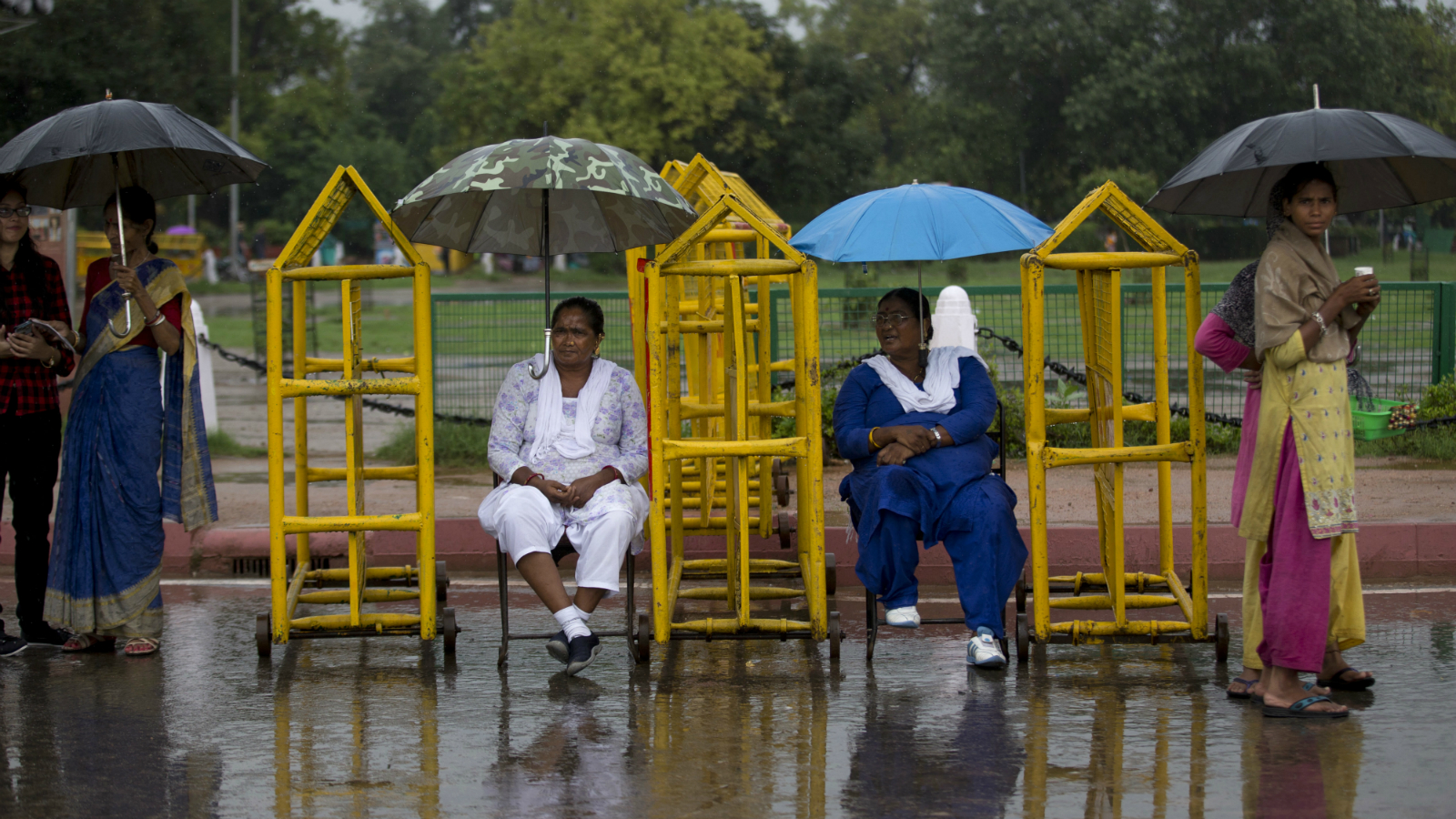Indian women take shelter from the rain under umbrellas, placed on police barricades, in New Delhi, India, Thursday, Sept. 1, 2016. Monsoon season in India begins in June and ends in October.
