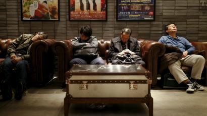 Men sleep in couches in a public seating area in a department store in Tokyo, Japan, March 17, 2016.