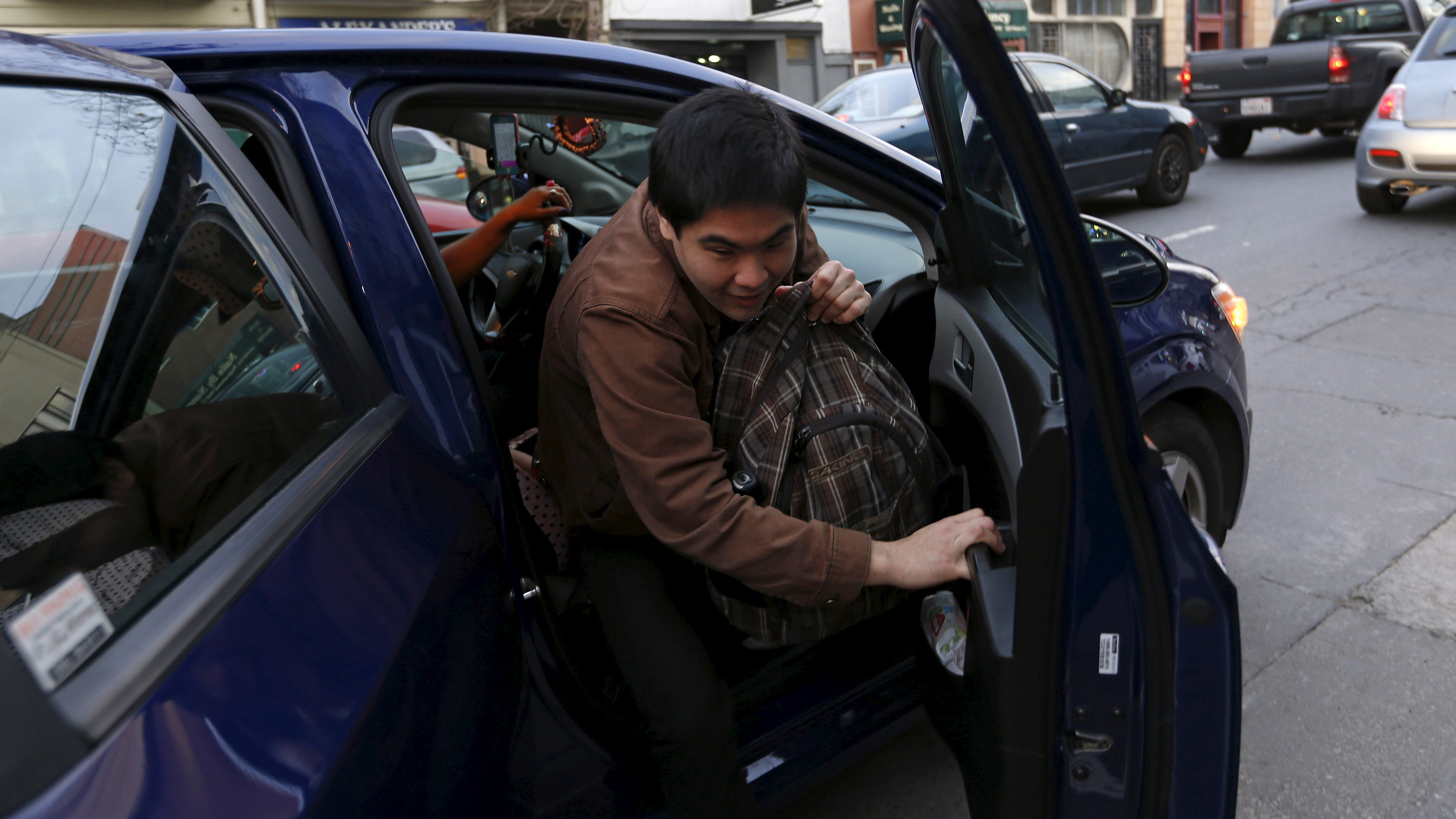 Lyft rider Adam Subiaga exits a car during a photo opportunity in San Francisco