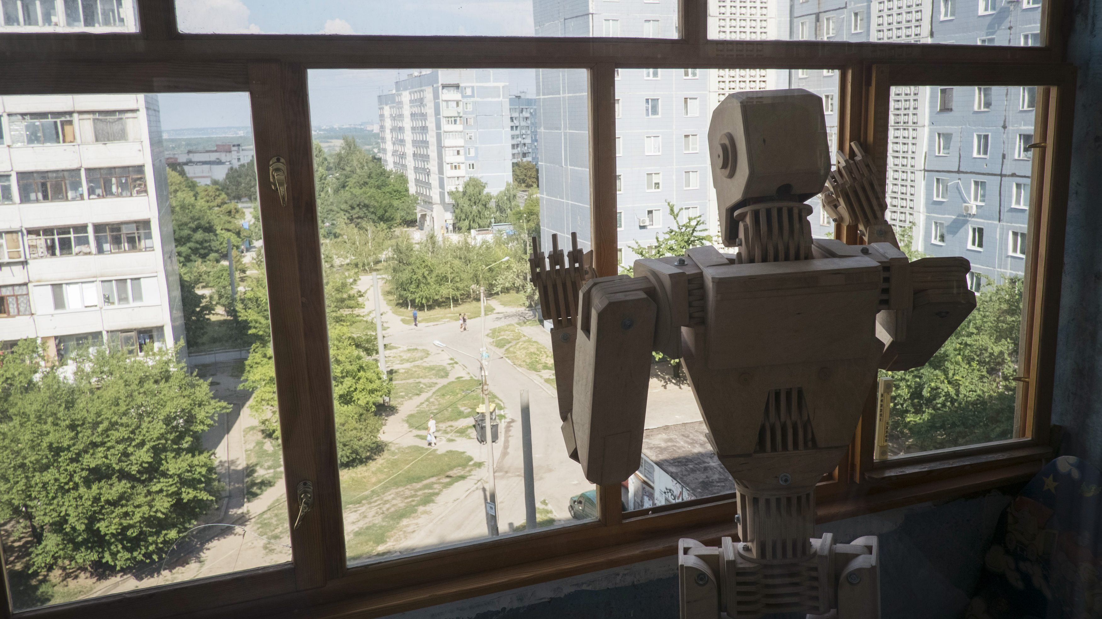 Wooden model Cylon is posed to look out of the window of the flat of its maker, Ukrainian Dmitry Balandin, in Zaporizhzhya August 6, 2013. It took Balandin, who works as a crane operator, six months to build the model from 500 parts. Balandin says he does not use blueprints and designs the parts as he works on them. He says he would love to build metal models but that is impossible to do so in his small apartment. He plays with Cylon as a child would play with a doll or Lego toy, and is now making a girlfriend for his model. He hopes to eventually build an entire model family and have them displayed at exhibitions and galleries.