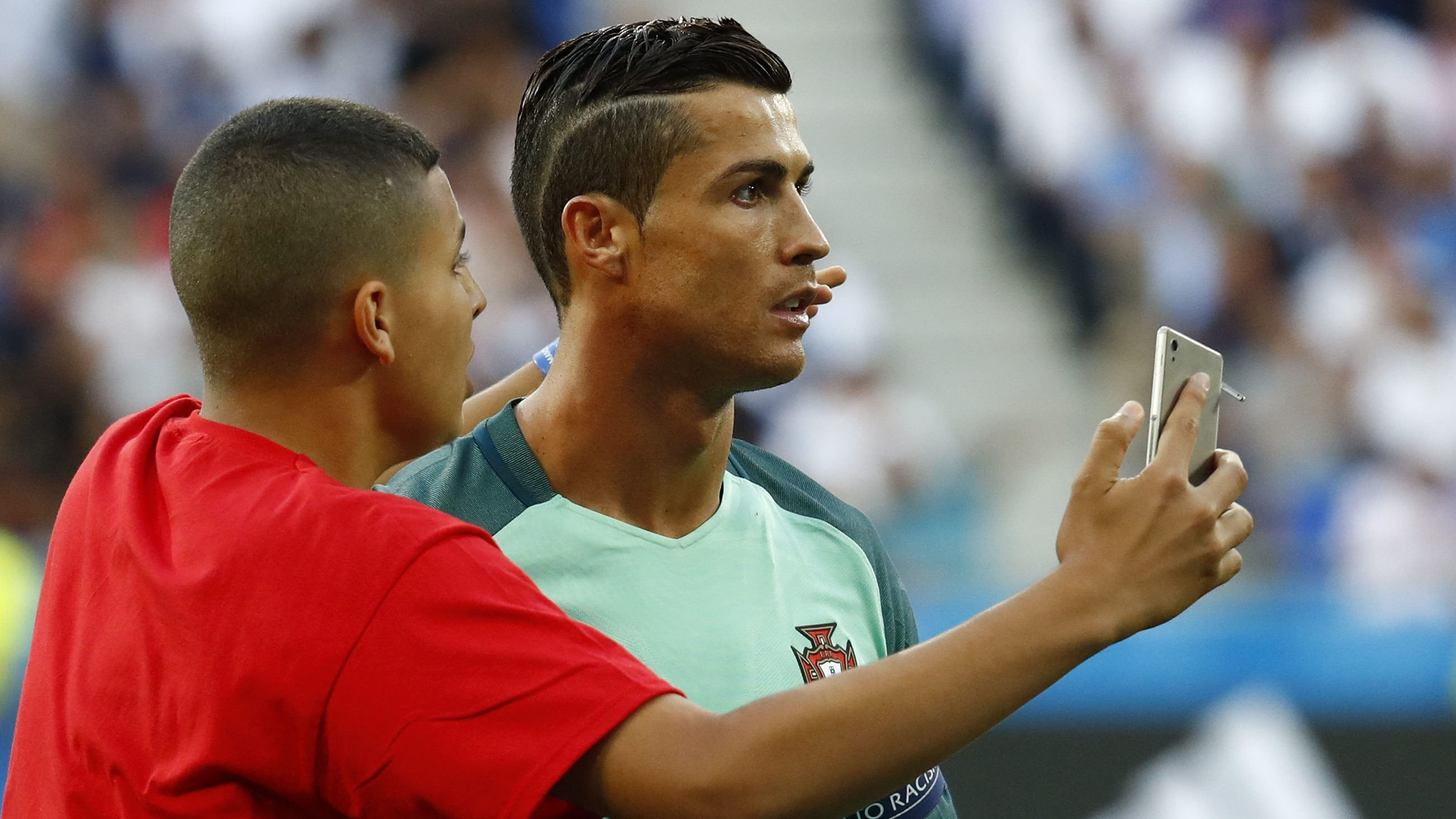 Football Soccer - Portugal v Wales - EURO 2016 - Semi Final - Stade de Lyon, Lyon, France - 6/7/16 Fan invades the pitch and attempts to take a selfie with Portugal's Cristiano Ronaldo before the game