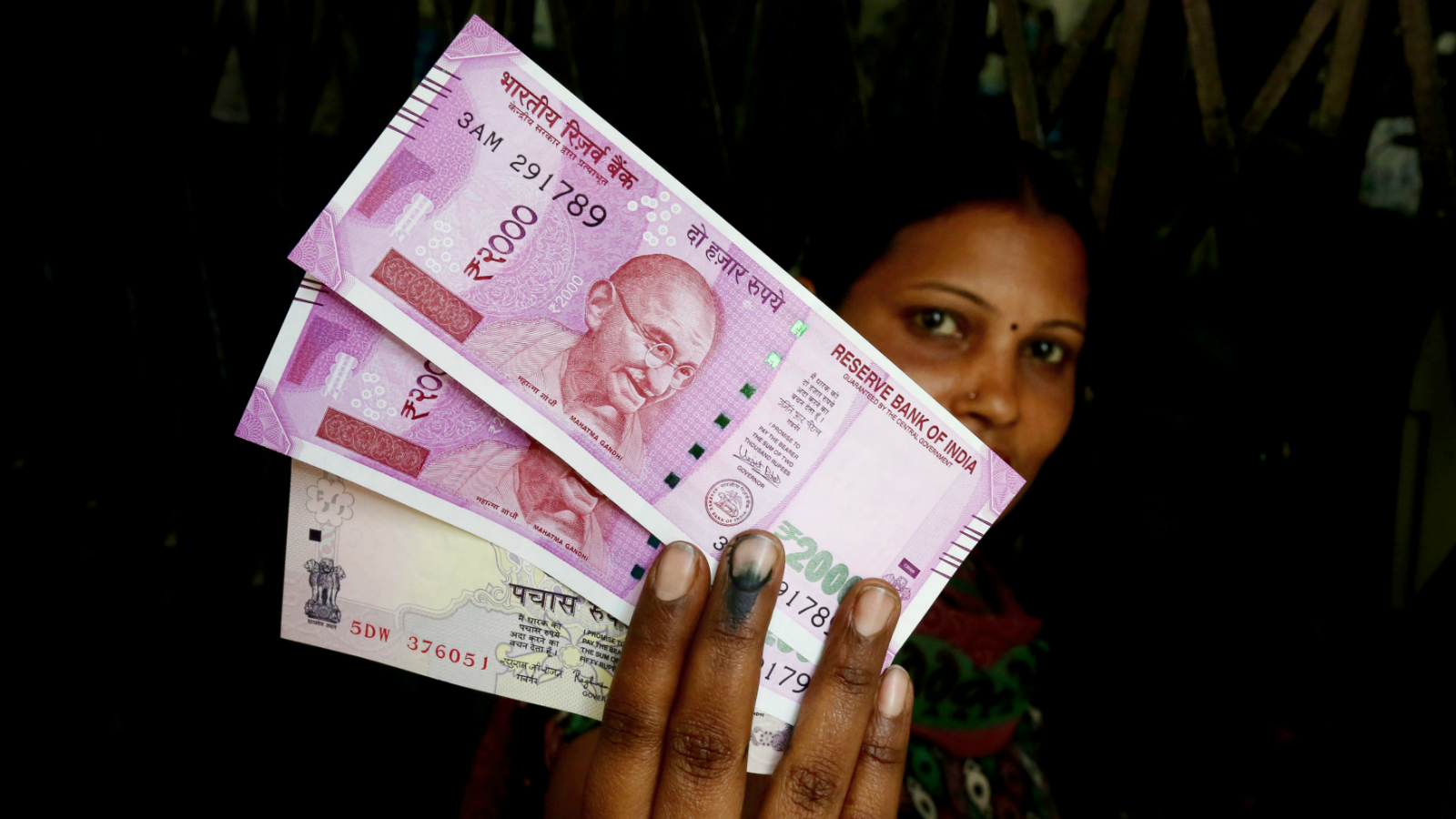 epa05633401 An Indian woman shows her inked finger as she holds new Indian rupee notes exchanged at a bank in Bangalore, India, 16 November 2016. Indian Bank officials started leaving an ink mark on fingers of people who have exchanged their discontinued Rupee notes for new ones. Indian Prime Minister Narendra Modi announced the elimination of the 500 and 1,000 rupee bills (7.37 and 14.73 US dollars, respectively), hours before the measure took effect at midnight 08 November, for the purpose of fighting against 'black money' (hidden assets) and corruption in the country. The decision sparked some protests, while storekeepers complained about dwindling sales because many citizens lack the cash to buy the most basic products, as lines get longer at ATMs and banks.