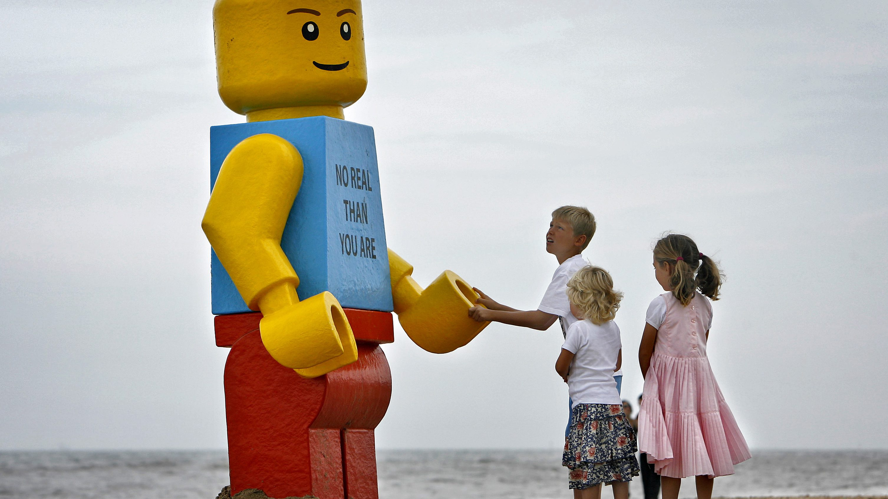 children play with giant Lego man