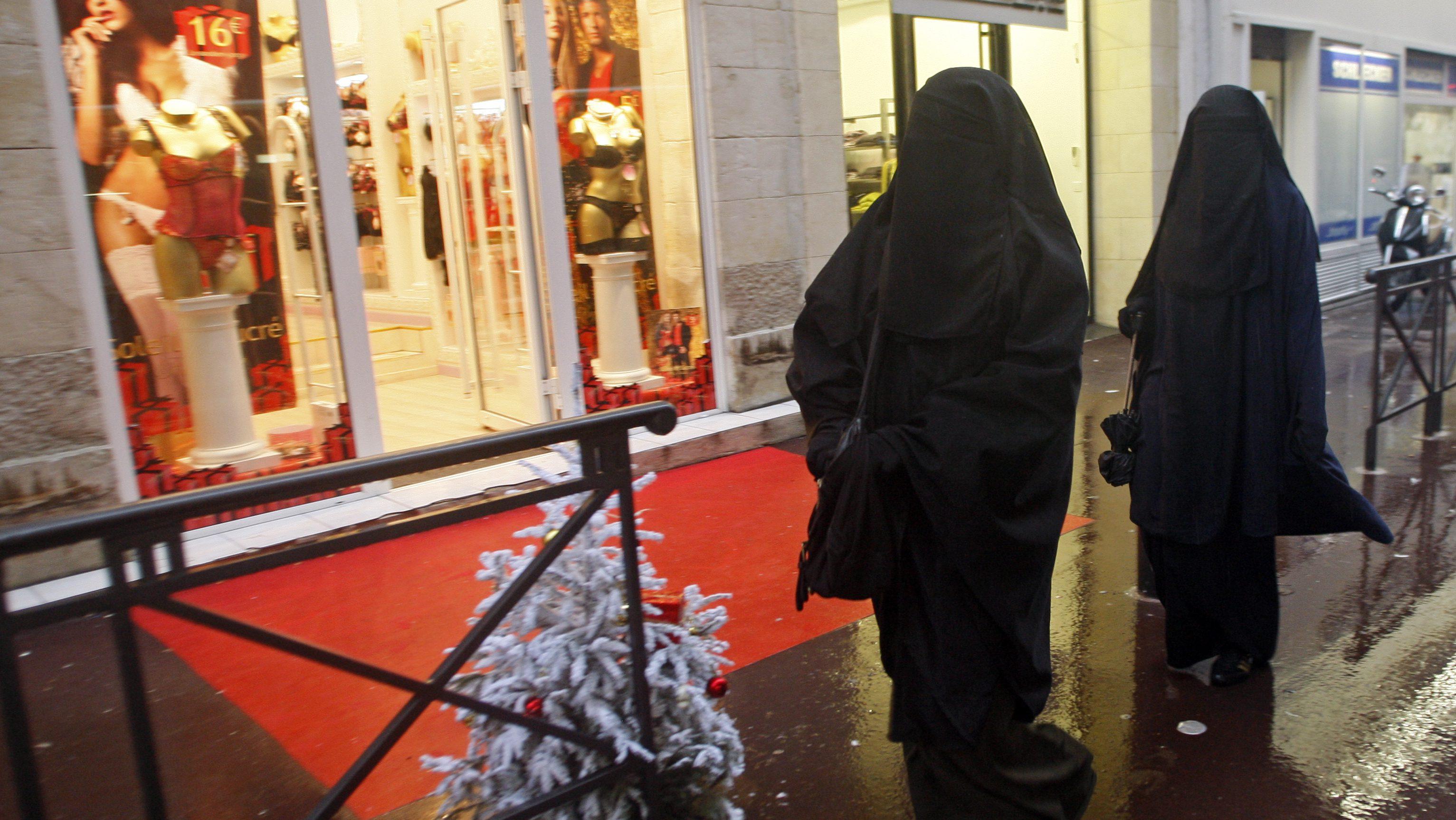 Women wearing niqabs walk past shops on the street in Marseille December 24, 2009.
