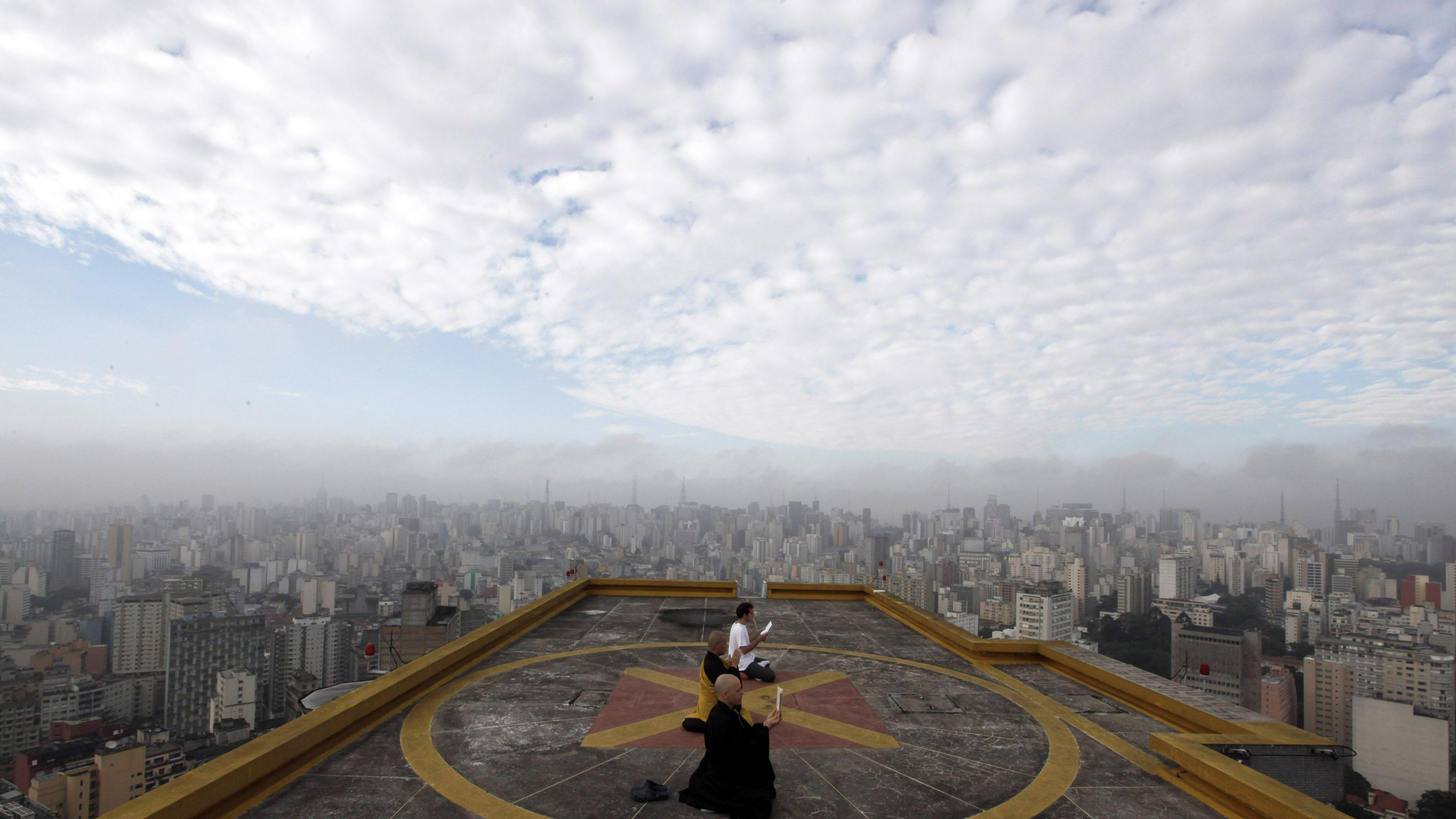 Buddhist monks Seigen, Jisho and Costa meditate on the helipad of Copan building in downtown Sao Paulo.