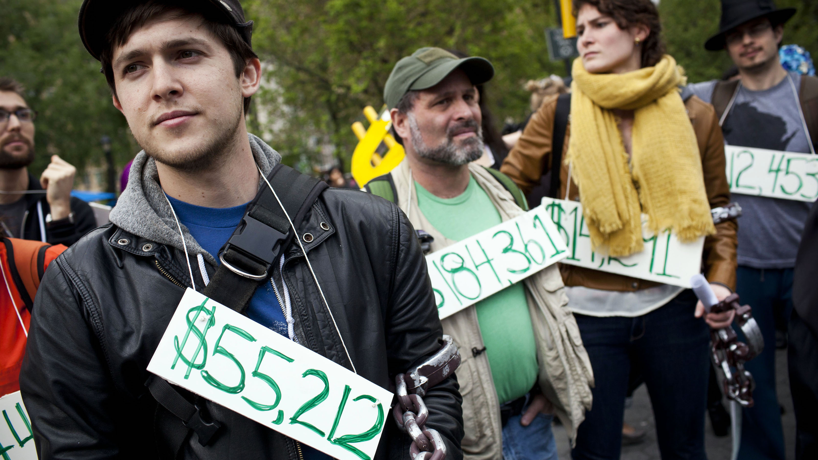 Occupy Wall Street demonstrators participating in a street-theater production wear signs around their neck representing their student debt during a protest against the rising national student debt in Union Square, in New York, April 25, 2012. The protest eventually marched to Wall Street; two people were arrested during the protest. REUTERS/Andrew Burton (UNITED STATES - Tags: CIVIL UNREST EDUCATION) - RTR3186L