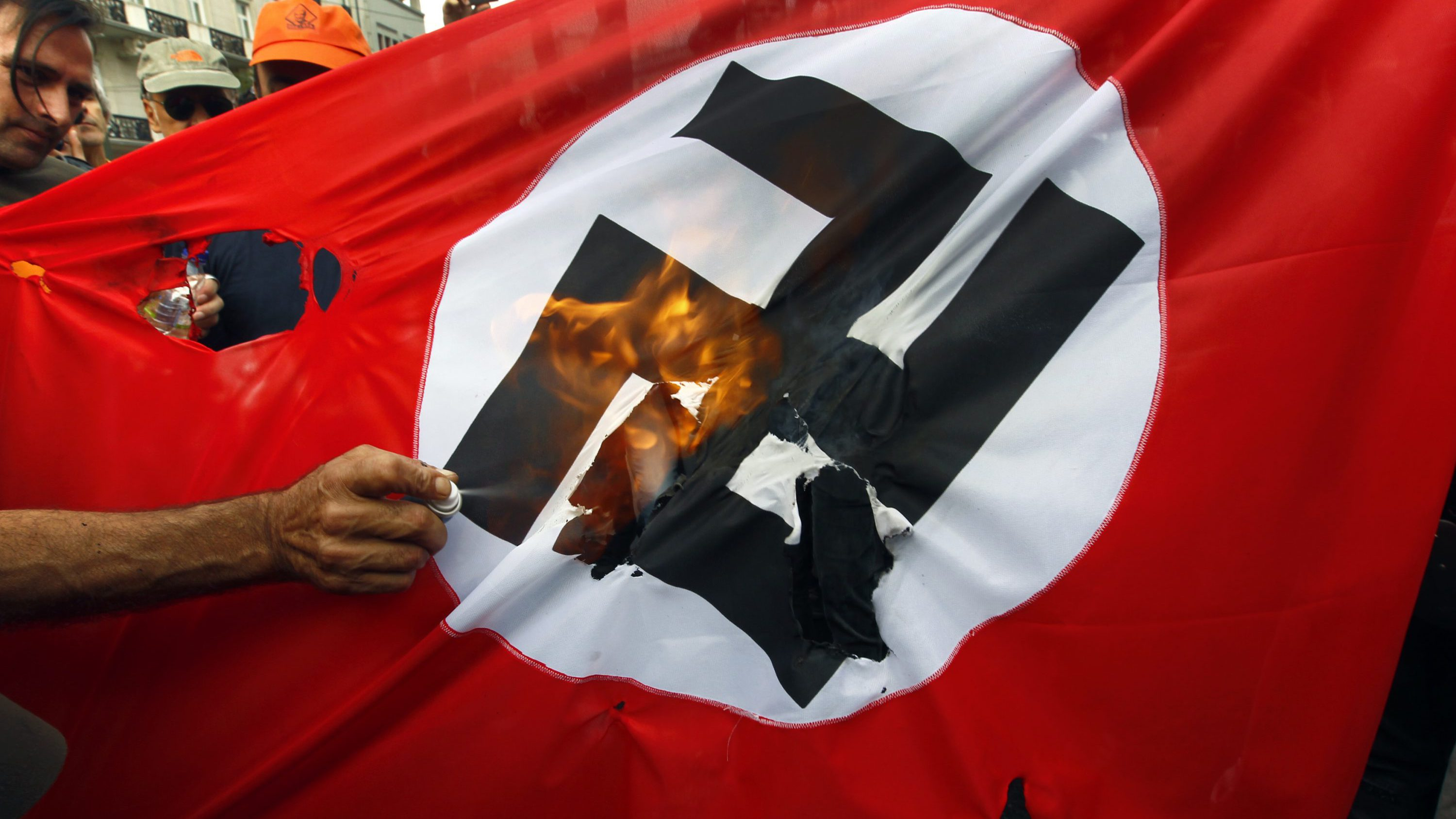 Demonstrators burn a flag emblazoned with a swastika during a demonstration against the visit of German Chancellor Angela Merkel in central Athens, October 9, 2012. Germany's Angela Merkel arrived in Greece on her first visit since Europe's debt crisis erupted here three years ago, braving protests to deliver a message of support - but no new money - to a nation hammered by recession and fighting to stay in the euro.