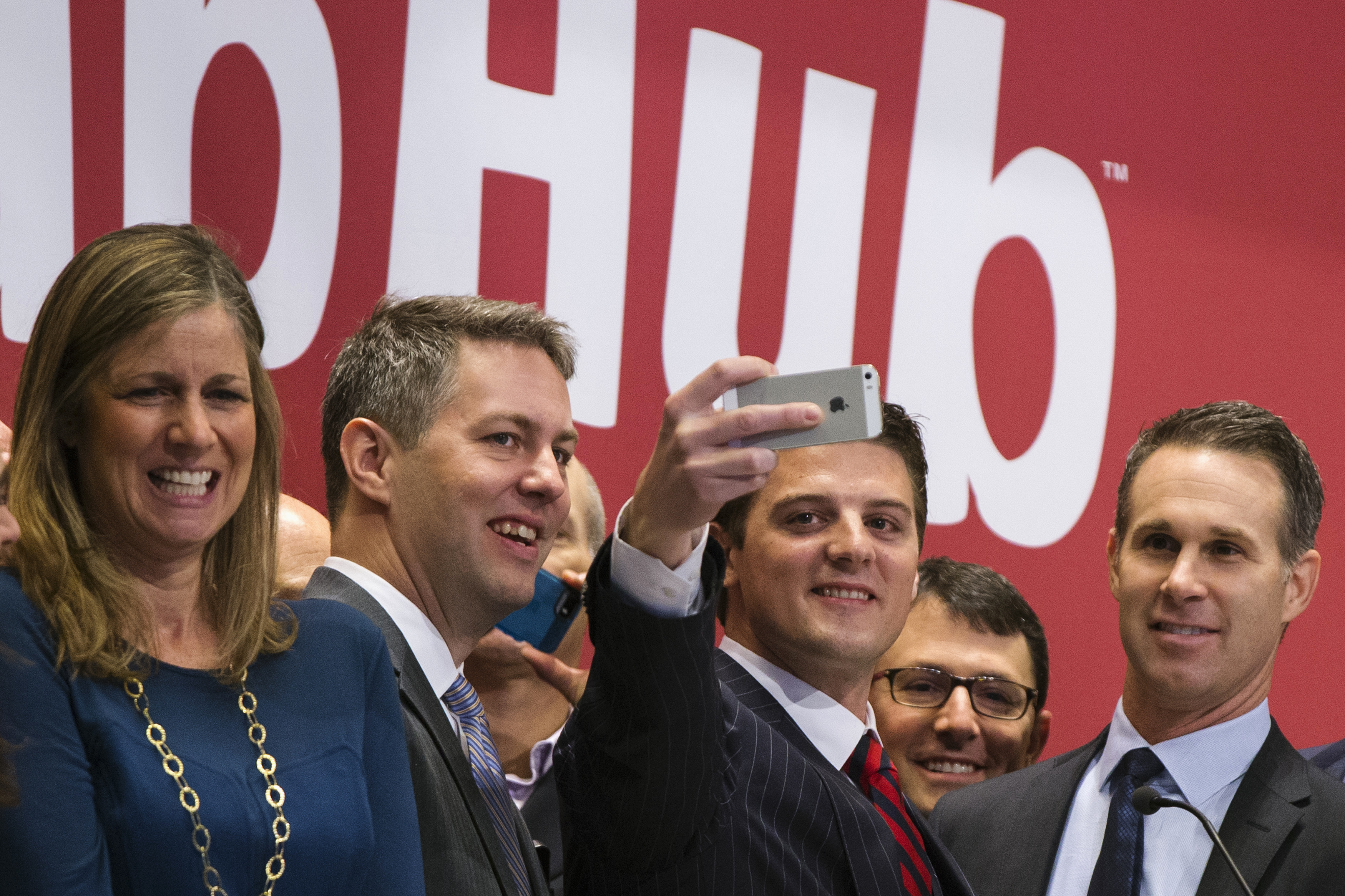 """GrubHub CEO Matt Maloney (2nd R) takes a """"selfie"""" photograph before ringing the opening bell, before the company's IPO on the floor of the New York Stock Exchange"""