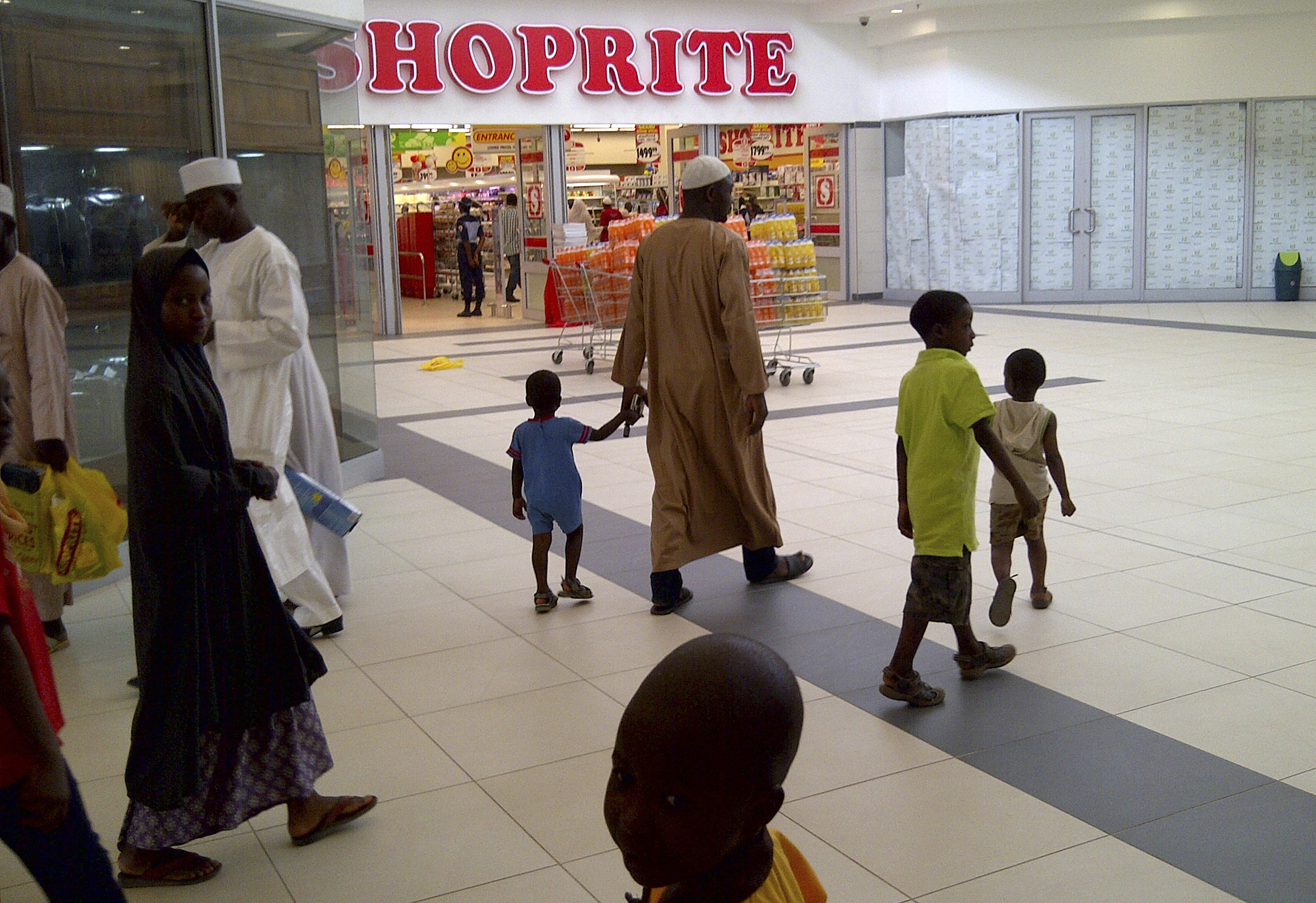 """A Nigerian family walks past a newly-opened Shoprite supermarket in Nigeria's northern city of Kano April 2, 2014. Kano is a dusty centuries-old Sahel belt metropolis that once offered gold, salt, slaves, leather and famed indigo-dyed textiles in its teeming markets at the end of an ancient caravan route linking Libya to black Africa south of the Sahara. Now, amid banner signs proclaiming """"lower prices you can trust"""", Kano consumers can wheel their carts between shelves replete with commercial brands from across the globe in a brand-new, air-conditioned Shoprite supermarket, anchoring a larger $85 million shopping mall development in the city. Picture taken April 2, 2014. REUTERS/Pascal Fletcher (NIGERIA - Tags: BUSINESS SOCIETY) - RTR3KGVD"""