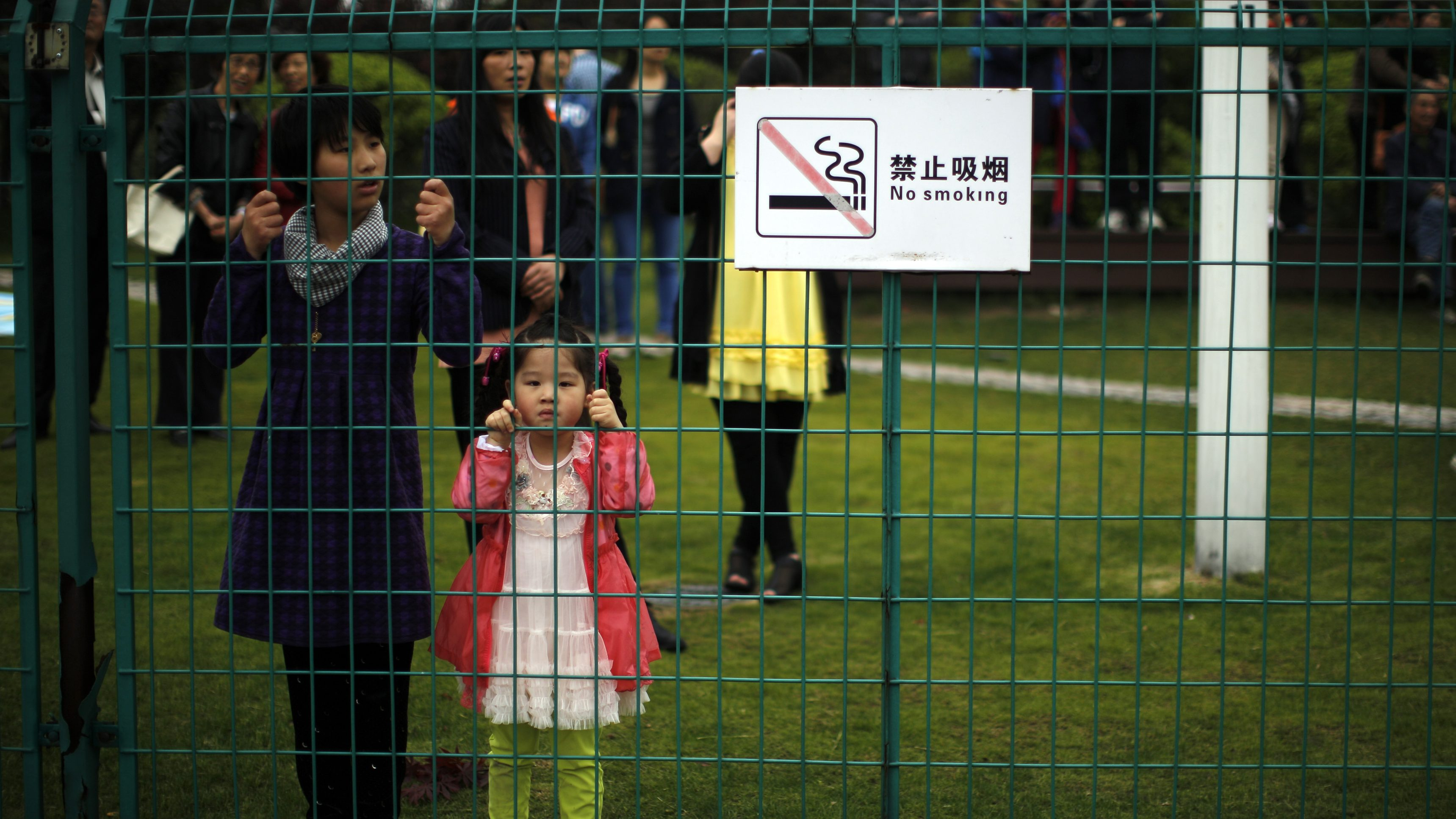 """Girls stand next to a """"No Smoking"""" sign at a park downtown Shanghai April 27, 2014. REUTERS/Carlos Barria (CHINA - Tags: SOCIETY TPX IMAGES OF THE DAY) - RTR3MT8Q"""