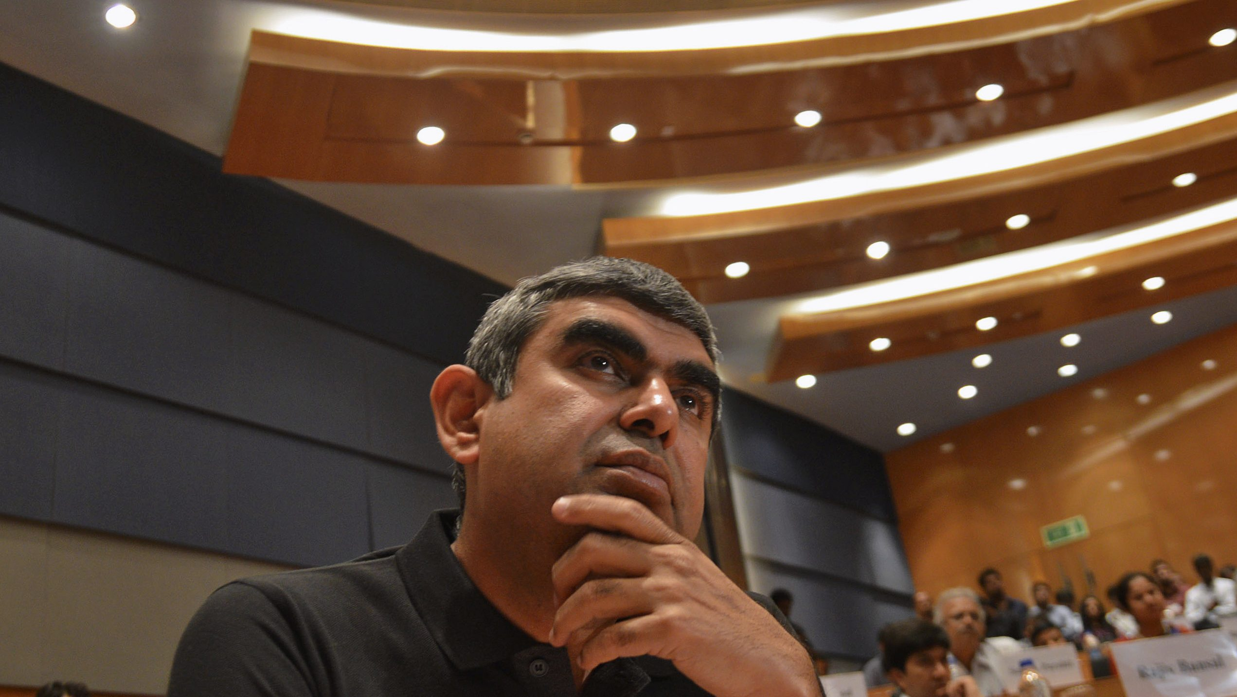 Infosys' newly appointed chief executive officer Vishal Sikka attends a news conference at company's headquarters in the southern Indian city of Bangalore June 12, 2014. Infosys Ltd, India's second-largest IT services exporter, has for the first time picked an outsider as chief executive officer, as it seeks to boost sales of high-margin services like cloud computing and stem a staff exodus. Sikka, a former member of executive board at German software company SAP AG, has the technical savvy to herald what analysts expect will be a strategy overhaul at Infosys, which, like its competitors Tata Consultancy Services Ltd and Wipro Ltd, has relied on labour-intensive, low-margin contracts from Western clients.