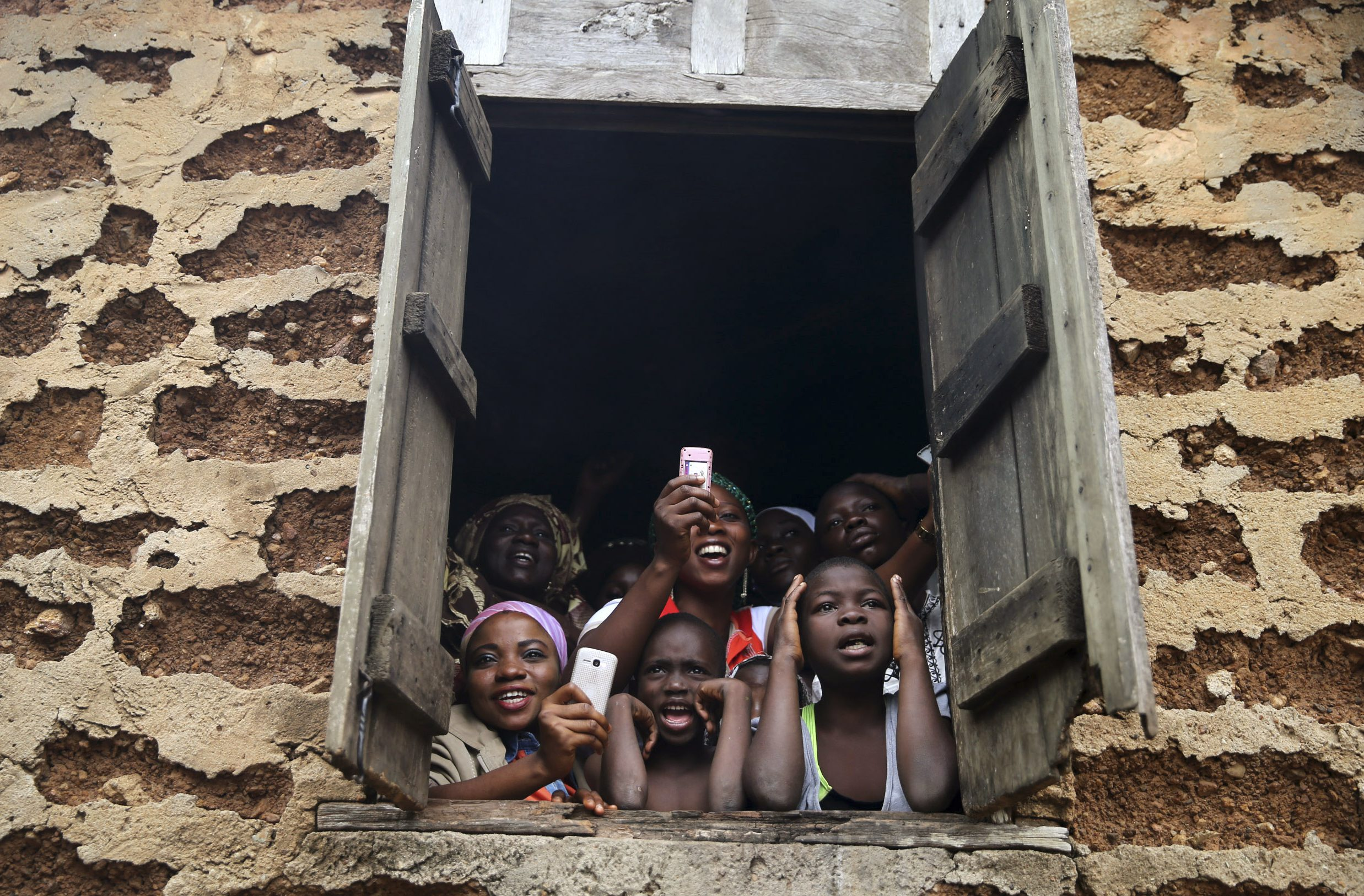 People gather at a window to watch a procession by followers of the Yoruba religion as part of a festival to celebrate the Osun river goddess in Osogbo, southwest Nigeria August 22, 2014.