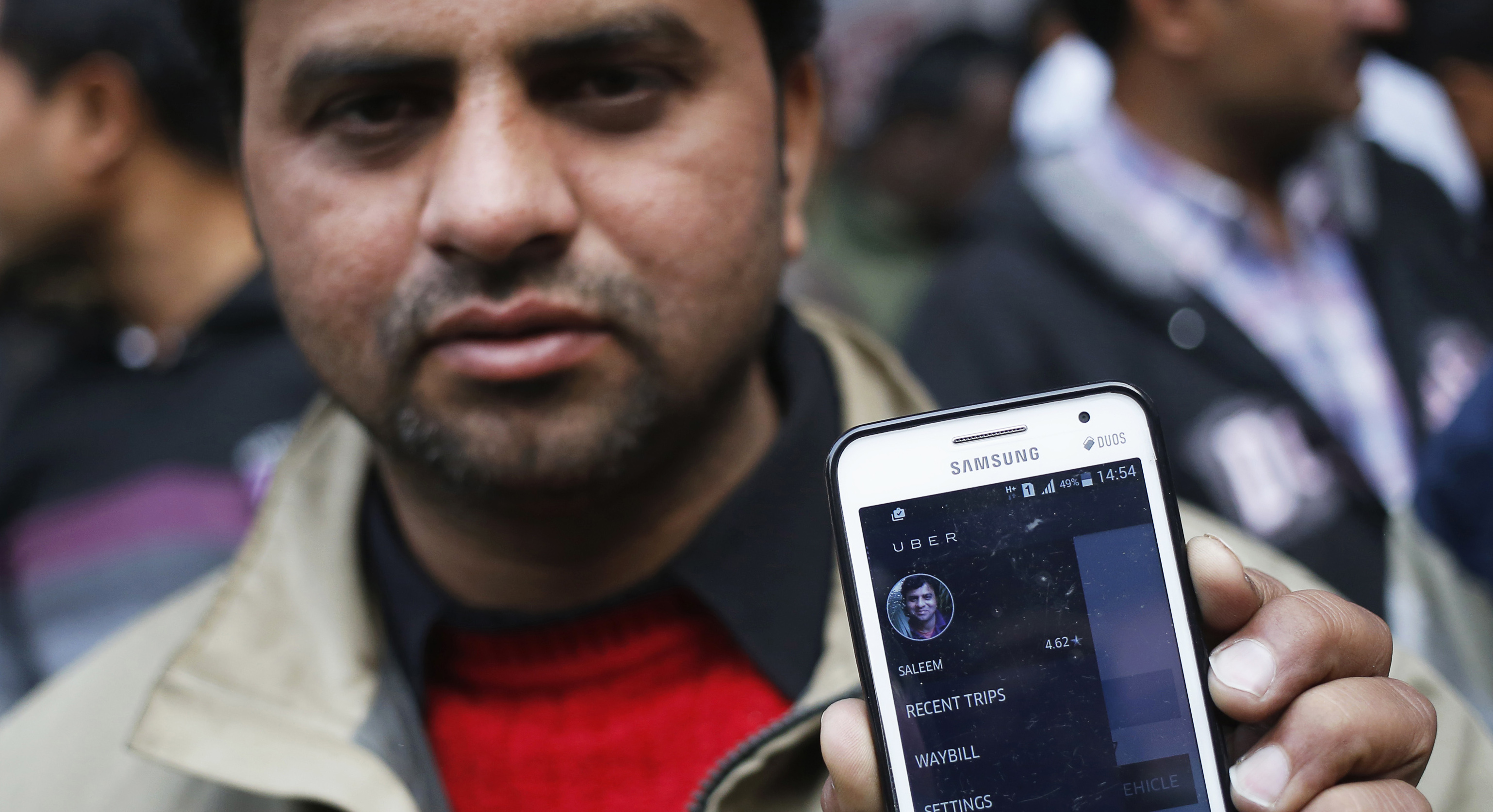 An Uber taxi driver shows an application software in his mobile phone used to track the taxi's location, during a protest against the ban on online taxi services, in New Delhi December 12, 2014. A ban on online taxi services in India, following the arrest in New Delhi of an Uber driver accused of rape, has brought uncertainty to the millions of dollars of international investment pumped into Uber's Indian rivals Ola and TaxiForSure.
