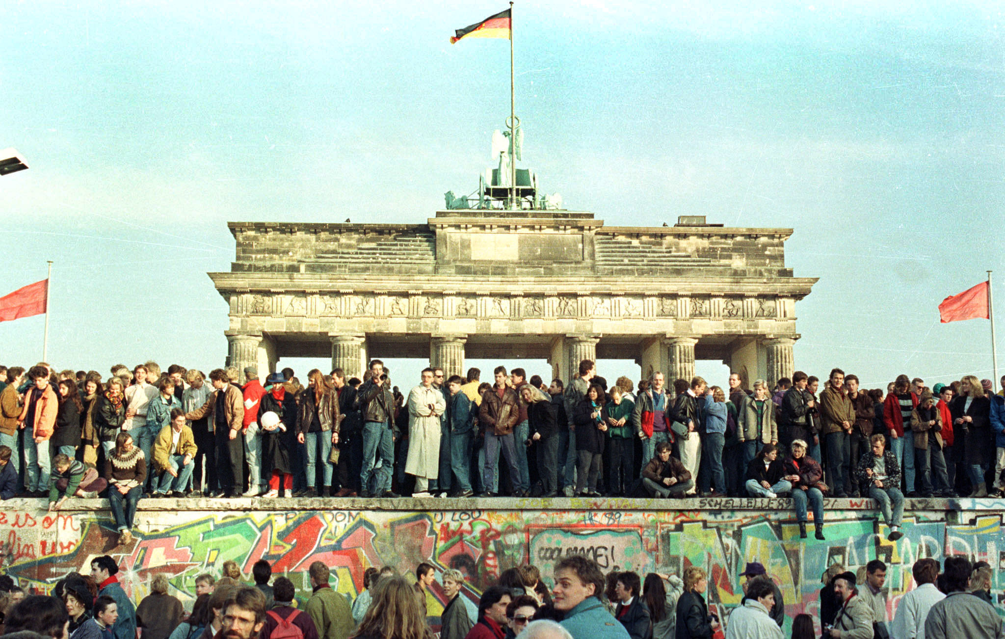 West Berlin citizens continue their vigil atop the Berlin Wall in front of the Brandeburg Gate in this November 10, 1989 file photo.