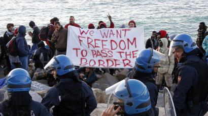 Migrants and activists hold a banner as they face off with Italian police on the seawall at the Saint Ludovic border crossing on the Mediterranean Sea between Ventimiglia, Italy and Menton, France, September 30, 2015.