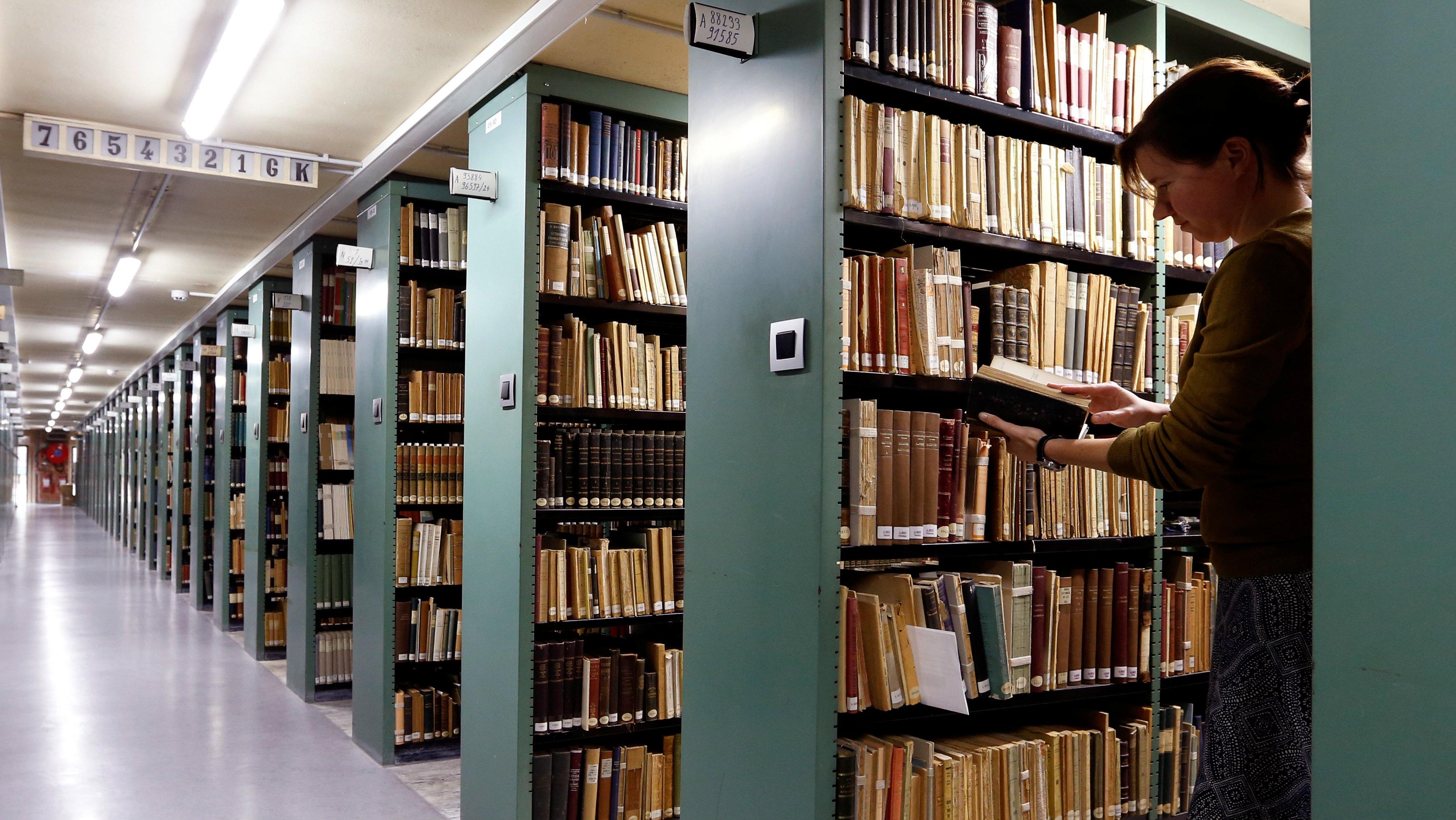 "A woman consults a book in the library of the university KU Leuven ""Katholieke Universiteit Leuven"" in Leuven, Belgium, June 8, 2016."