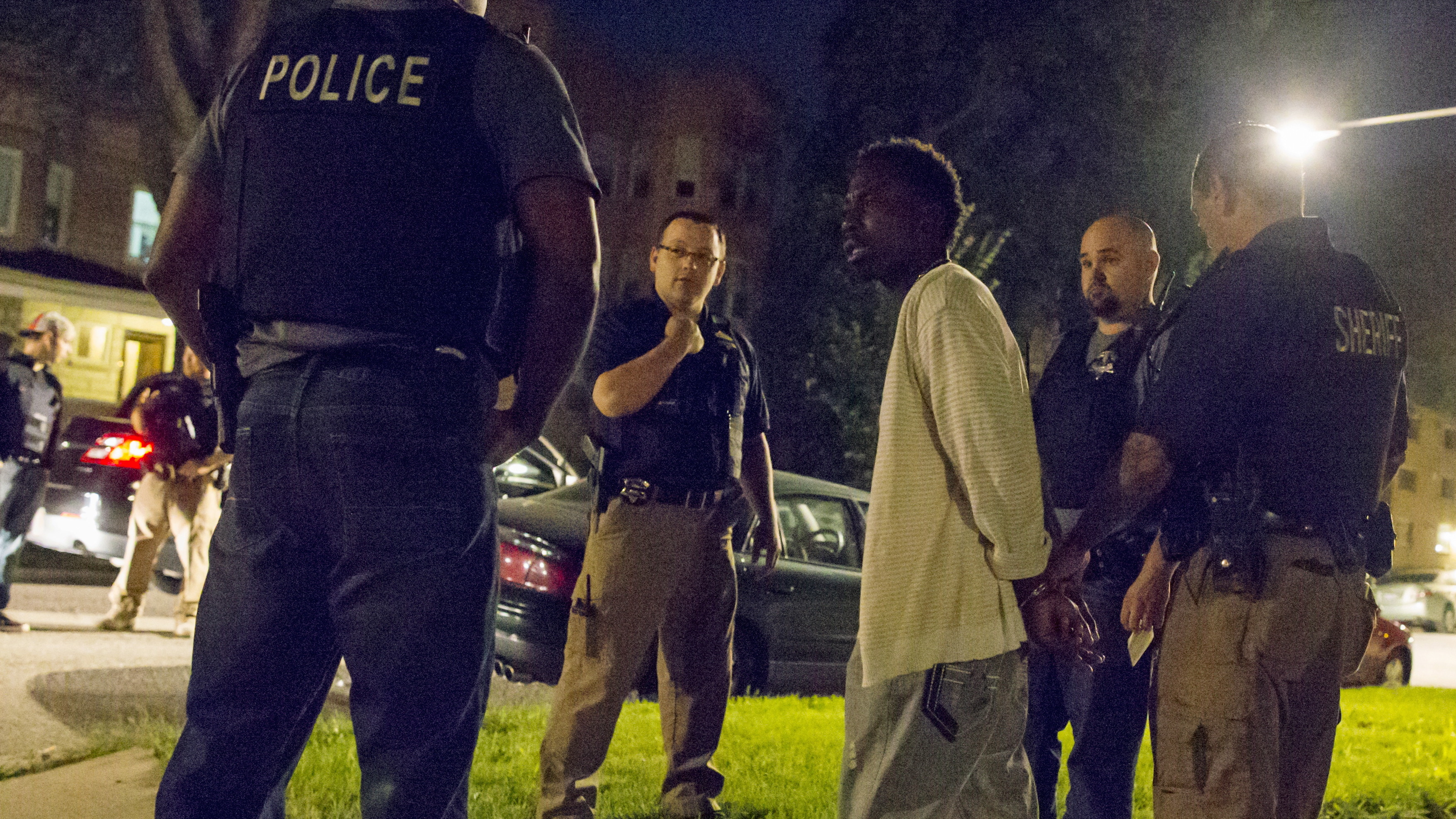 Cook County Sheriff police officers handcuff and question a man who walked up to them while officers where conducting an unrelated street stop in the Austin neighborhood in Chicago, Illinois, United States, September 9, 2015.