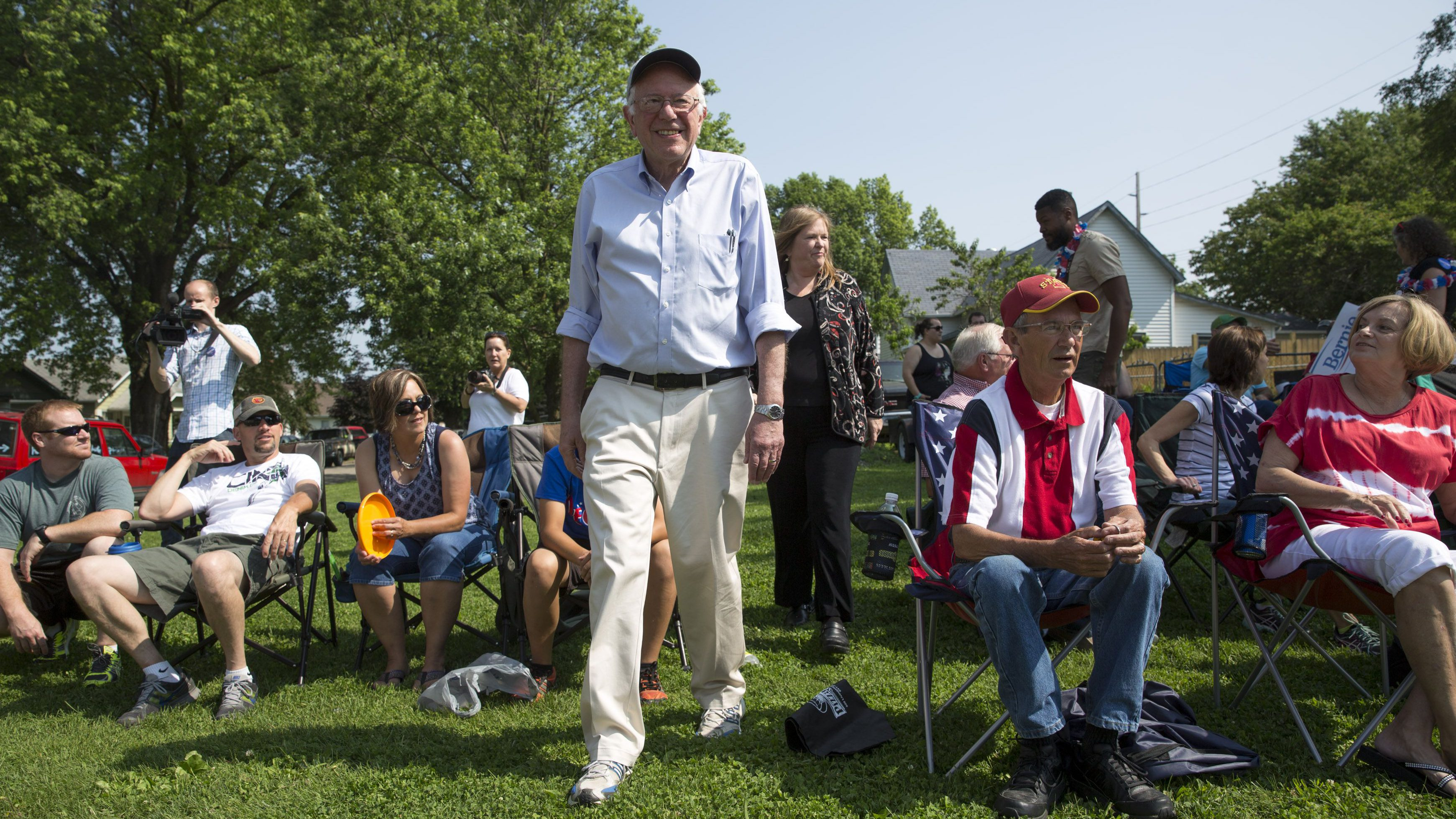 Democratic presidential hopeful Sen. Bernie Sanders walks through the crowd along the parade route during the Independence Day Parade in Creston, Iowa