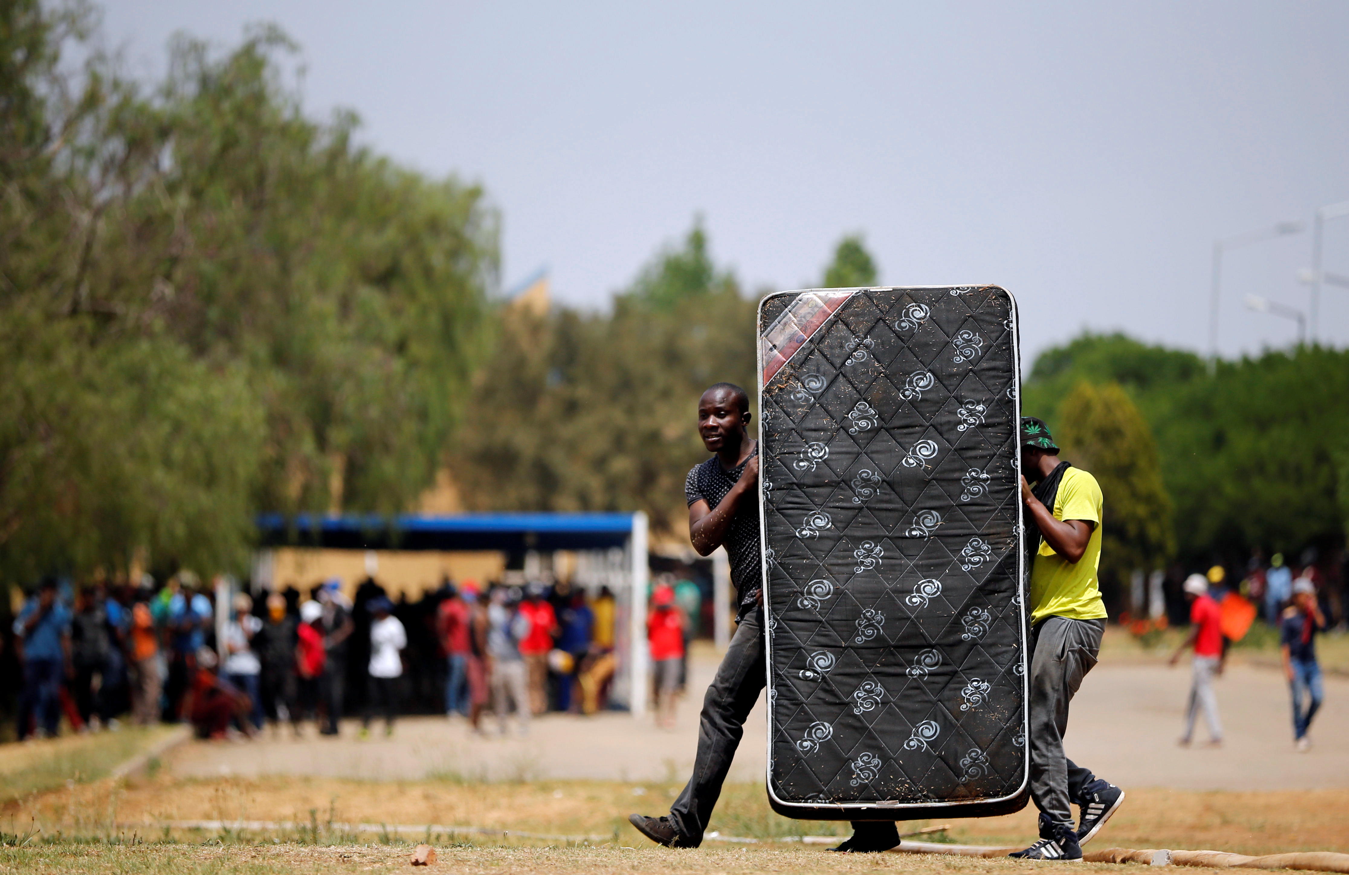 Protesters use a mattress as a cover during clashes with police officers, as students demand free education, at the Vaal University of Technology in Vanderbijlpark, South of Johannesburg, South Africa, October 13, 2016.