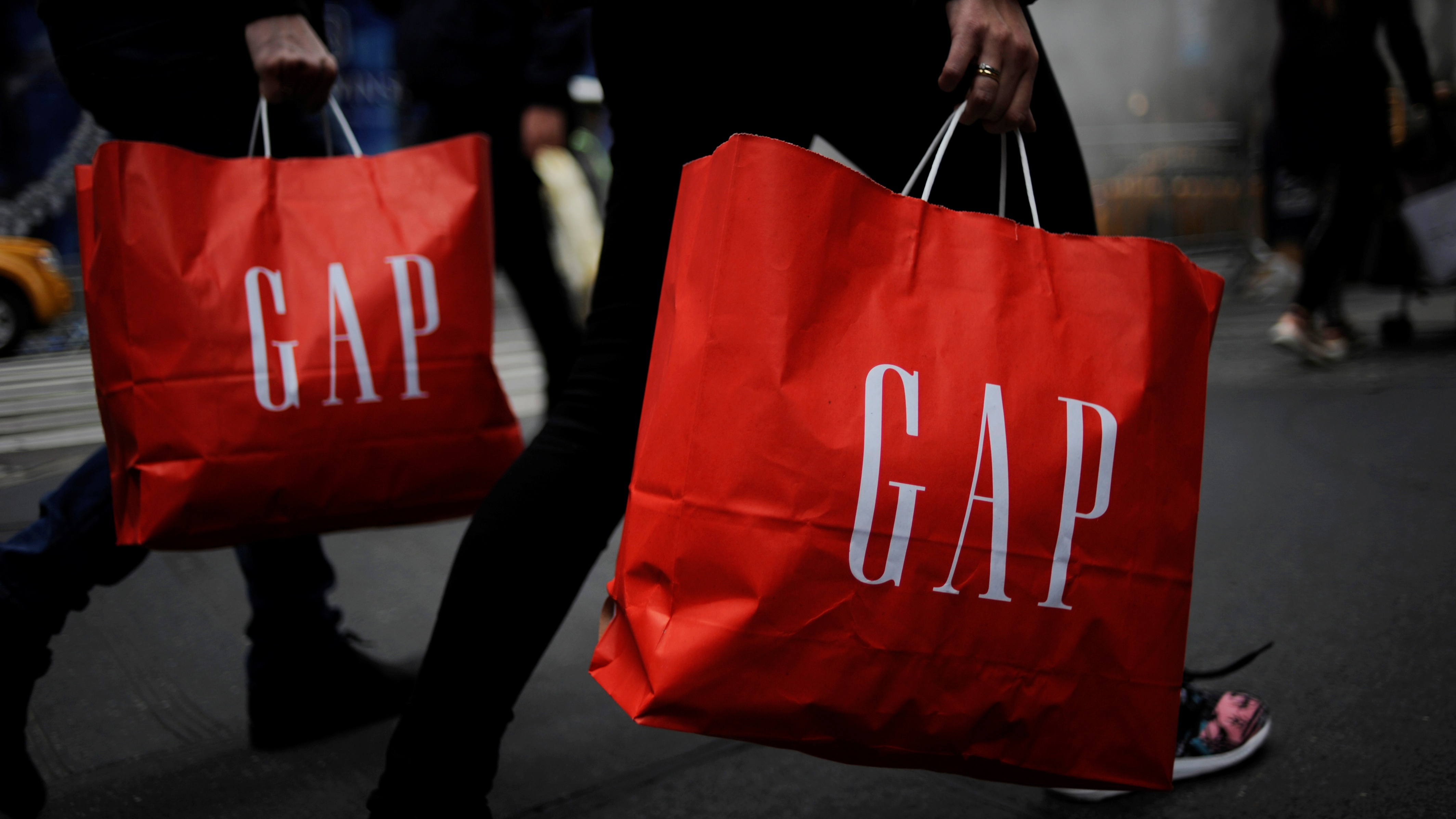 Shoppers carry bags from a Gap store as they walk along Fifth Avenue in the Manhattan borough of New York, U.S., November 20, 2016. REUTERS/Mark Kauzlarich