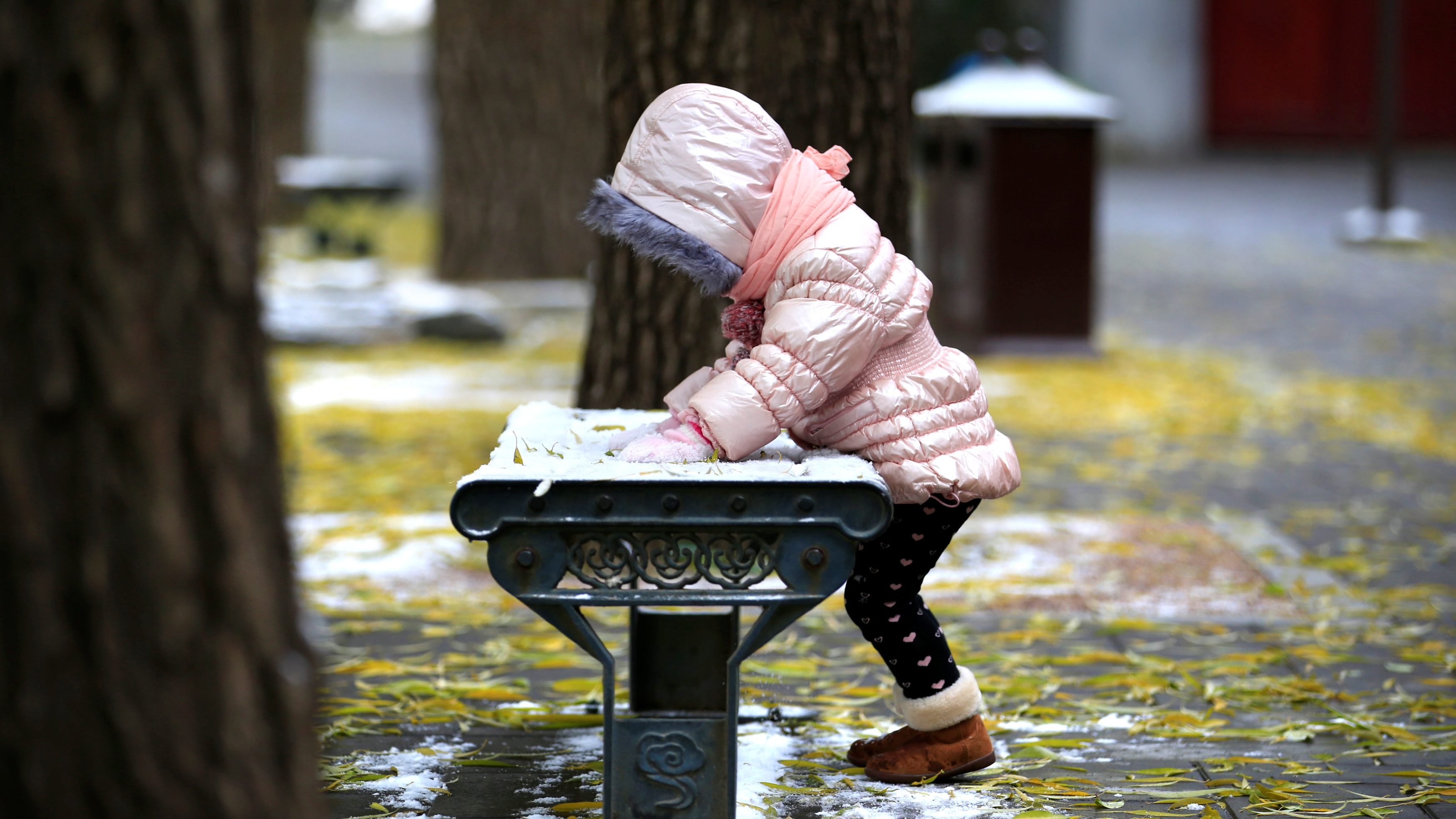 A girl plays with snow at Beihai Park in central Beijing