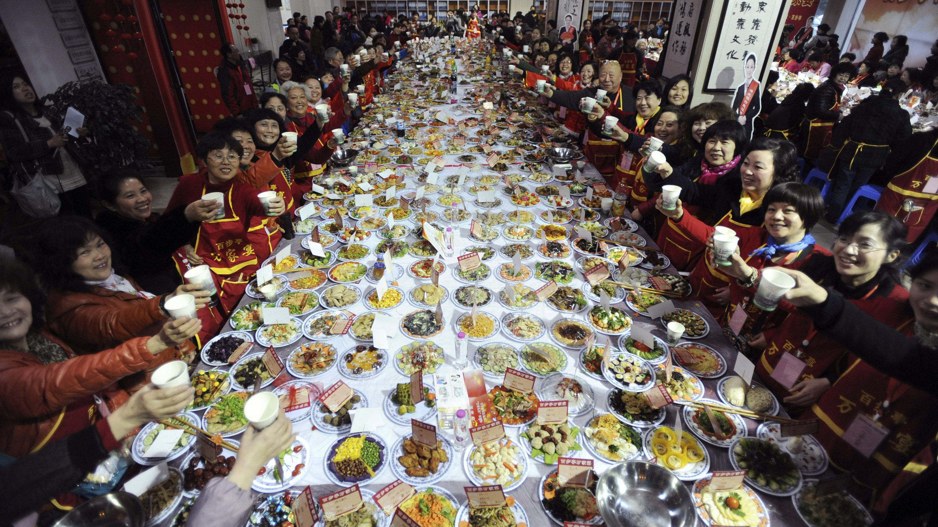 """Residents raise their glasses as they pose for photographs at a table full of dishes during a """"Ten thousand families dinner"""" organized by a local community to celebrate the upcoming Chinese Lunar New Year, in Wuhan, Hubei province January 24, 2014. A residential community in Wuhan hosted the mass dinner on Friday serving over 30,000 people with over 11,000 dishes of food cooked by the families of the community, local media reported. Picture taken January 24, 2014."""