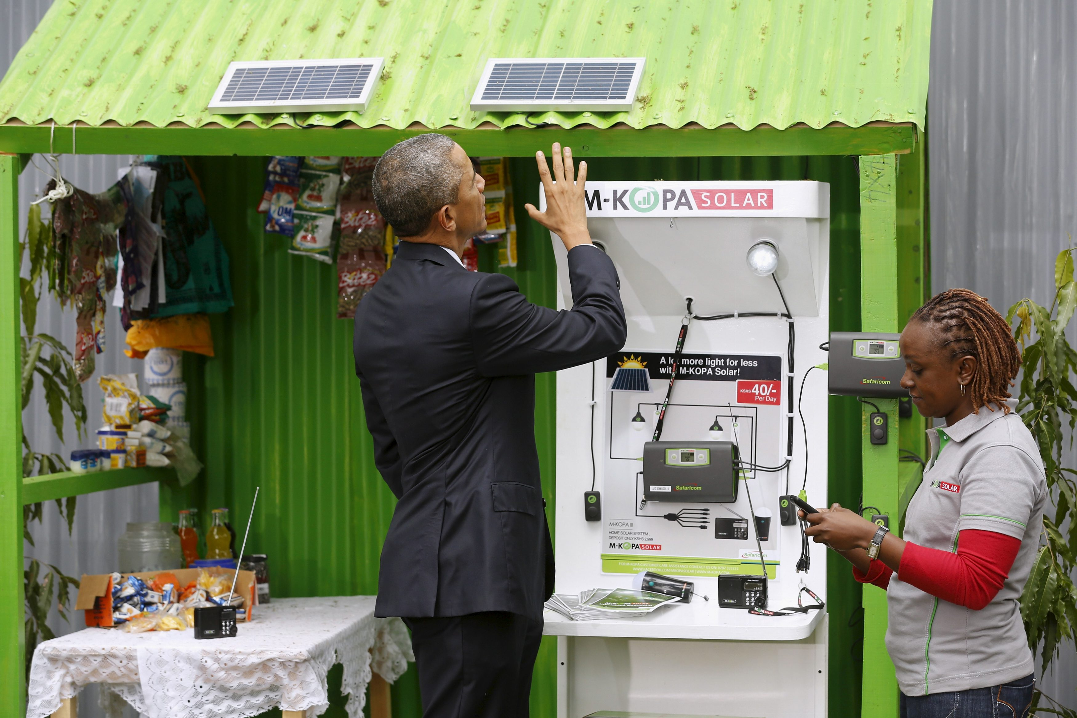 U.S. President Barack Obama (L) talks with a solar power businessperson at the Power Africa Innovation Fair at the United Nations compound in Nairobi, Kenya July 25, 2015.