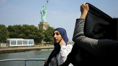Woman in a hijab near the Statue of Liberty.